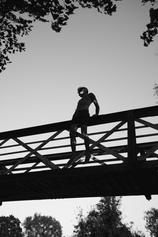 grayscale photography of man sitting on edge of bridge