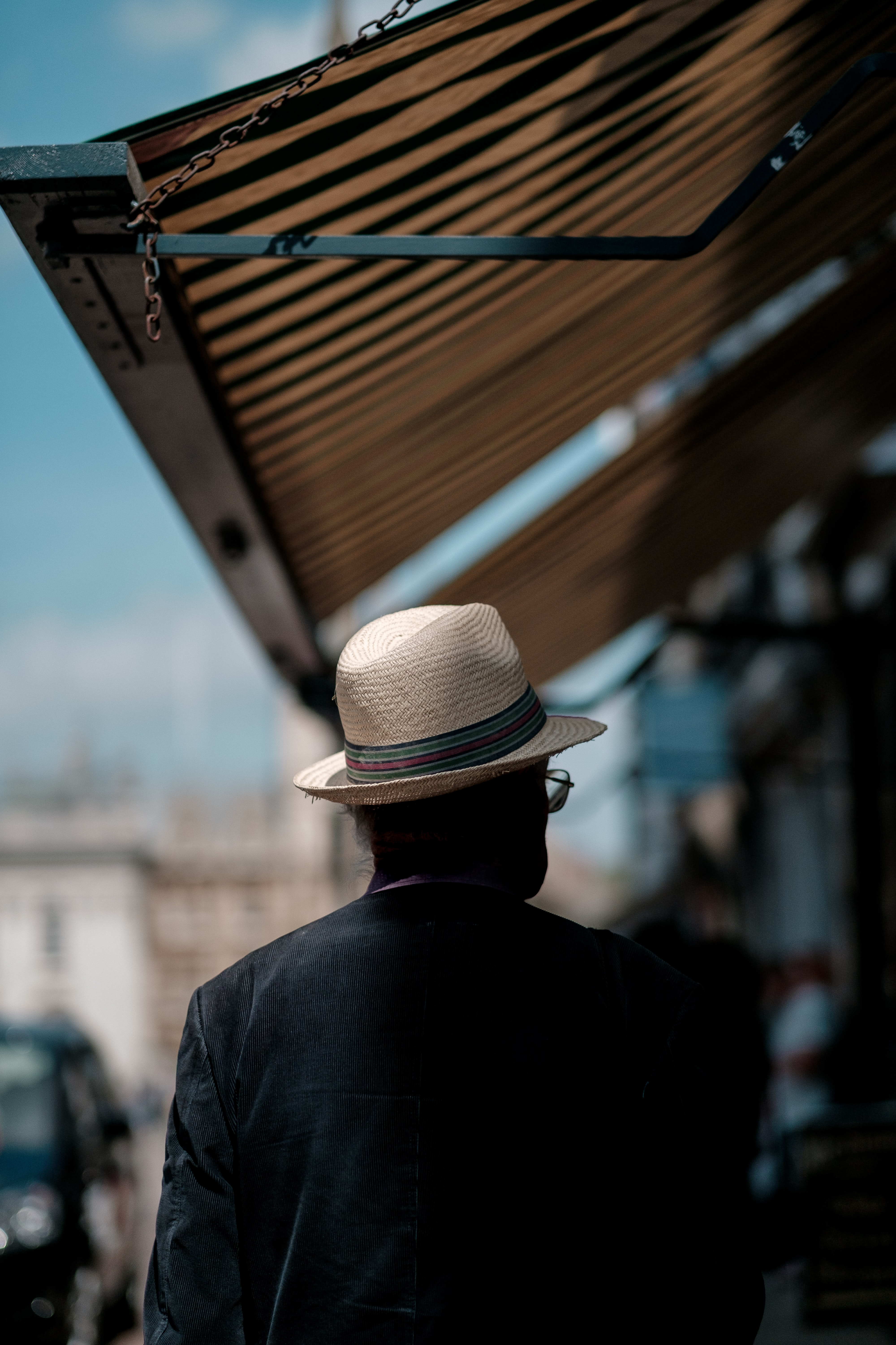 A man in a Panama hat on a sidewalk under an awning