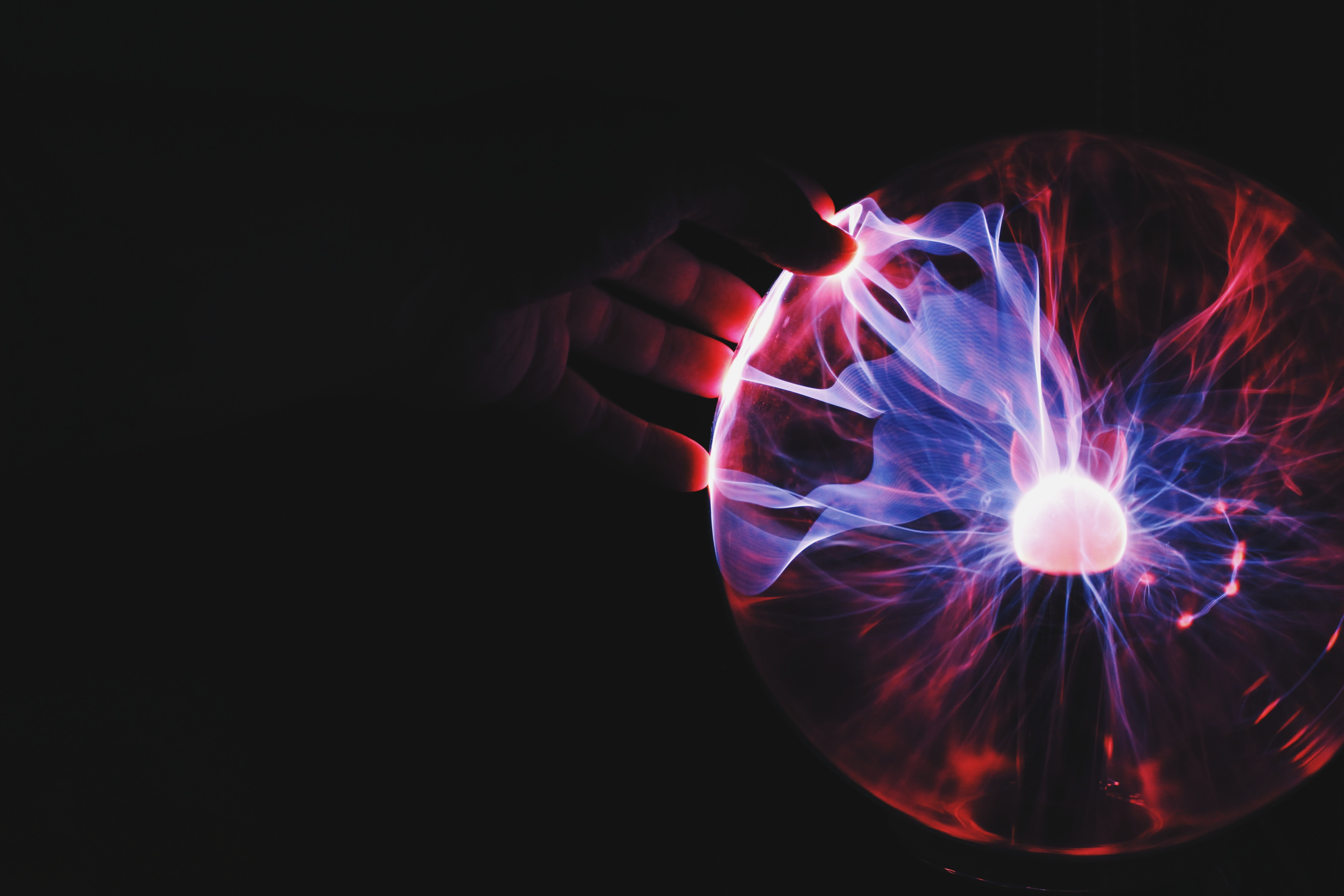 A hand touching an orb pulsating with blue and red energy