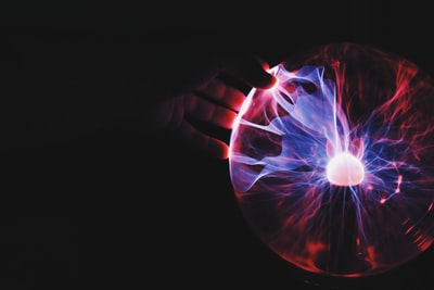human hand holding plasma ball technology teams background