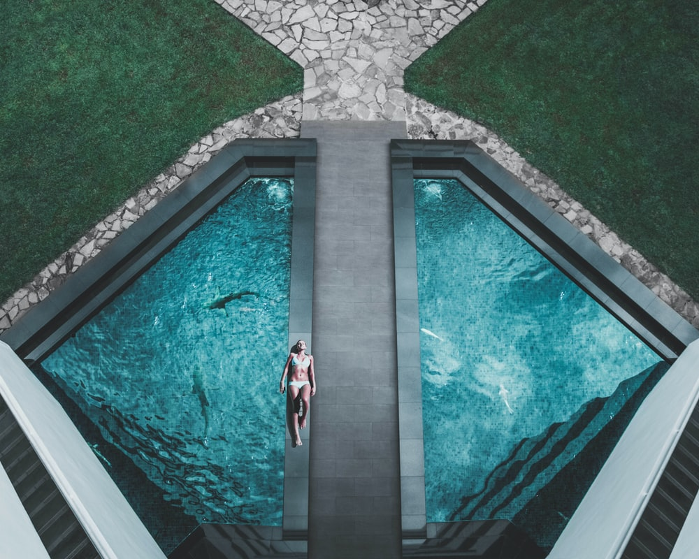 bird's eye view of woman lying on floor beside swimming pool