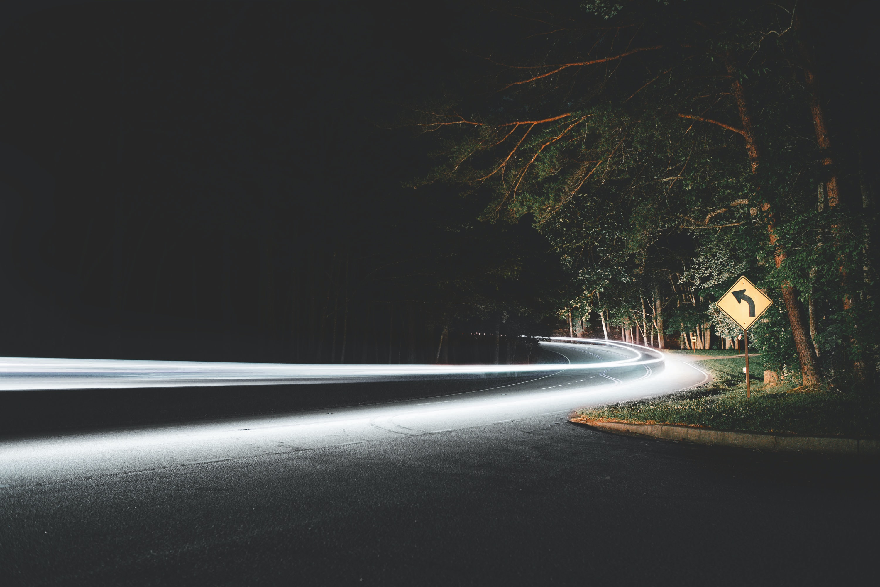 A time exposure shot of a street, with a turn sign signaling toward Kings Mountain