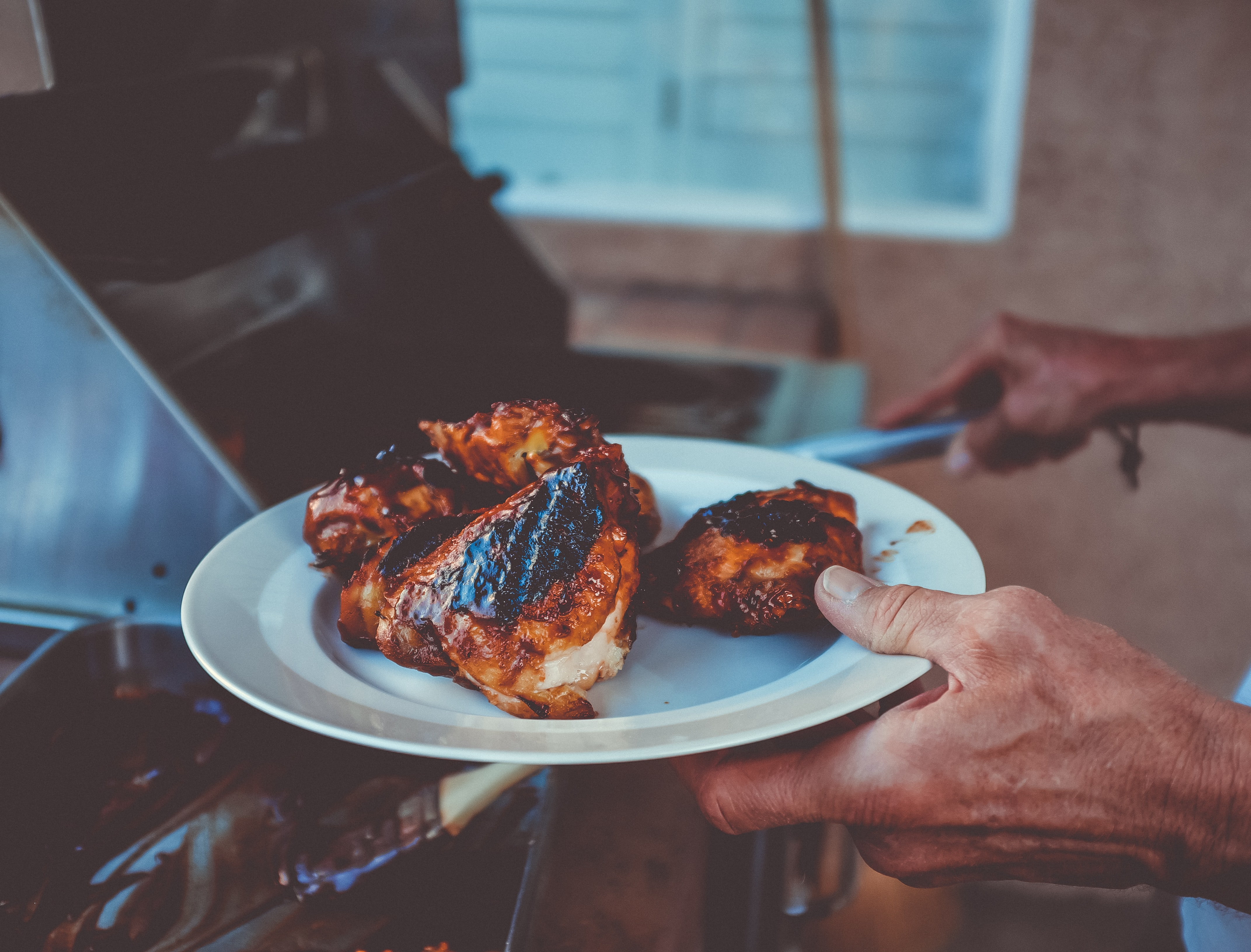 Hand holding a plate of BBQ chicken breasts coming off a grill in Green Valley South