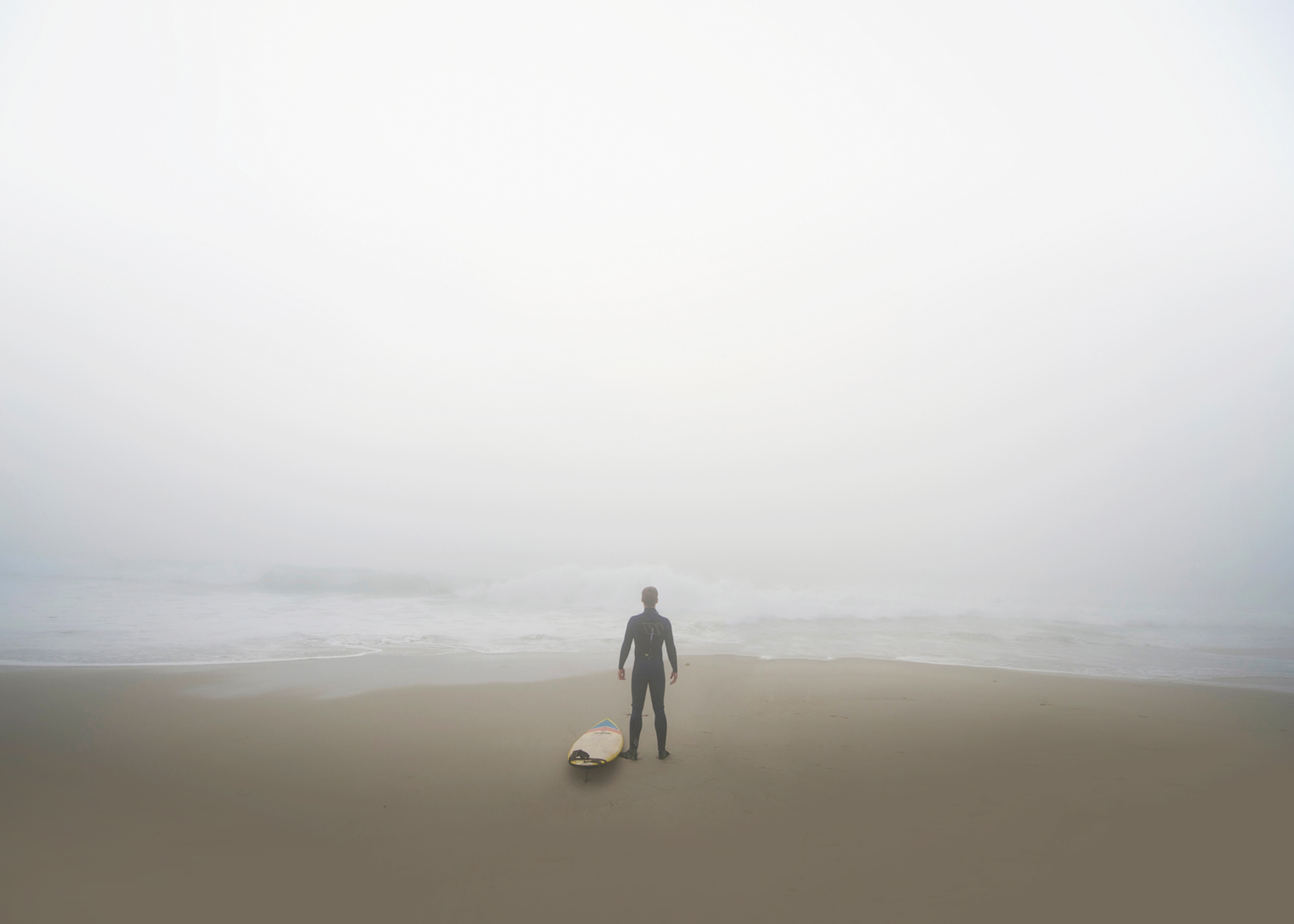Surfer stands on the ocean shore on a cloudy day in San Diego