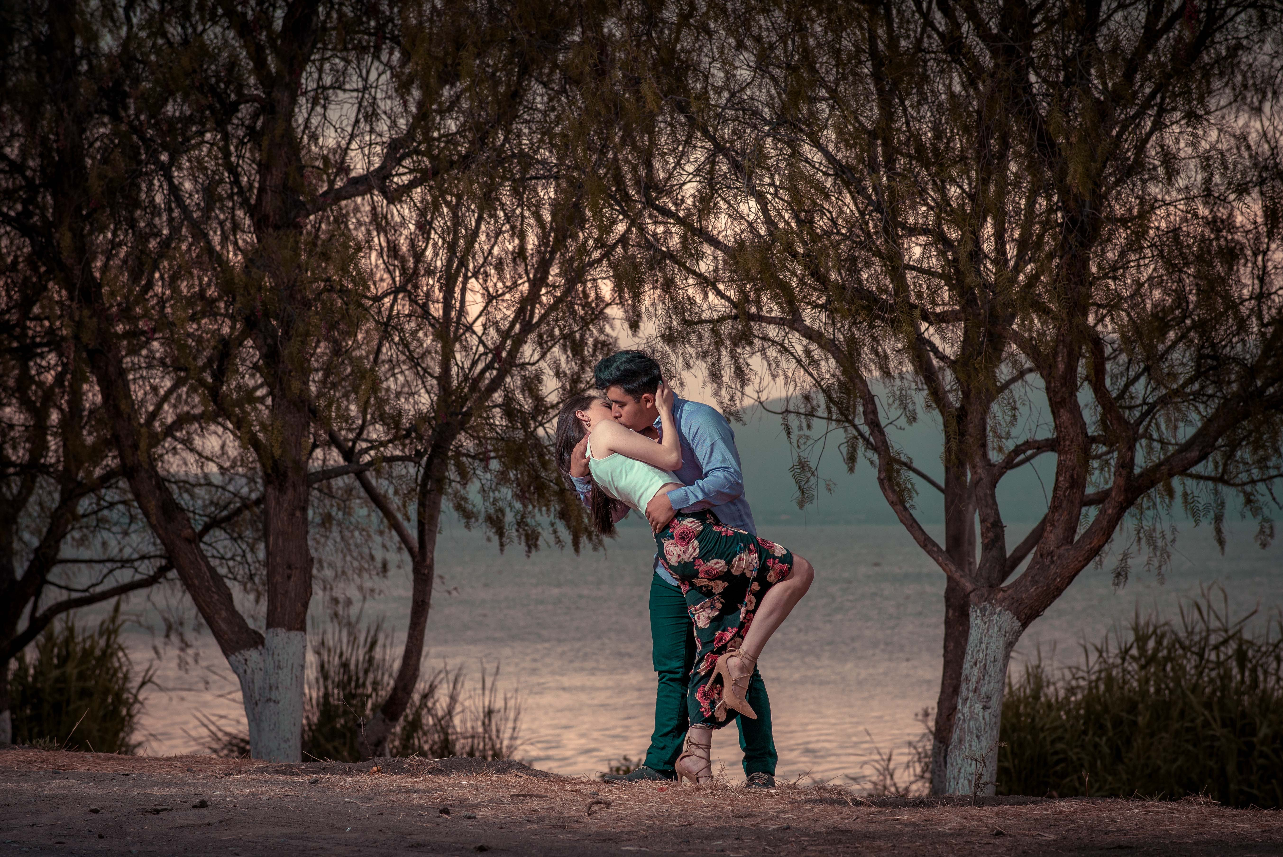 couple kissing in front of trees