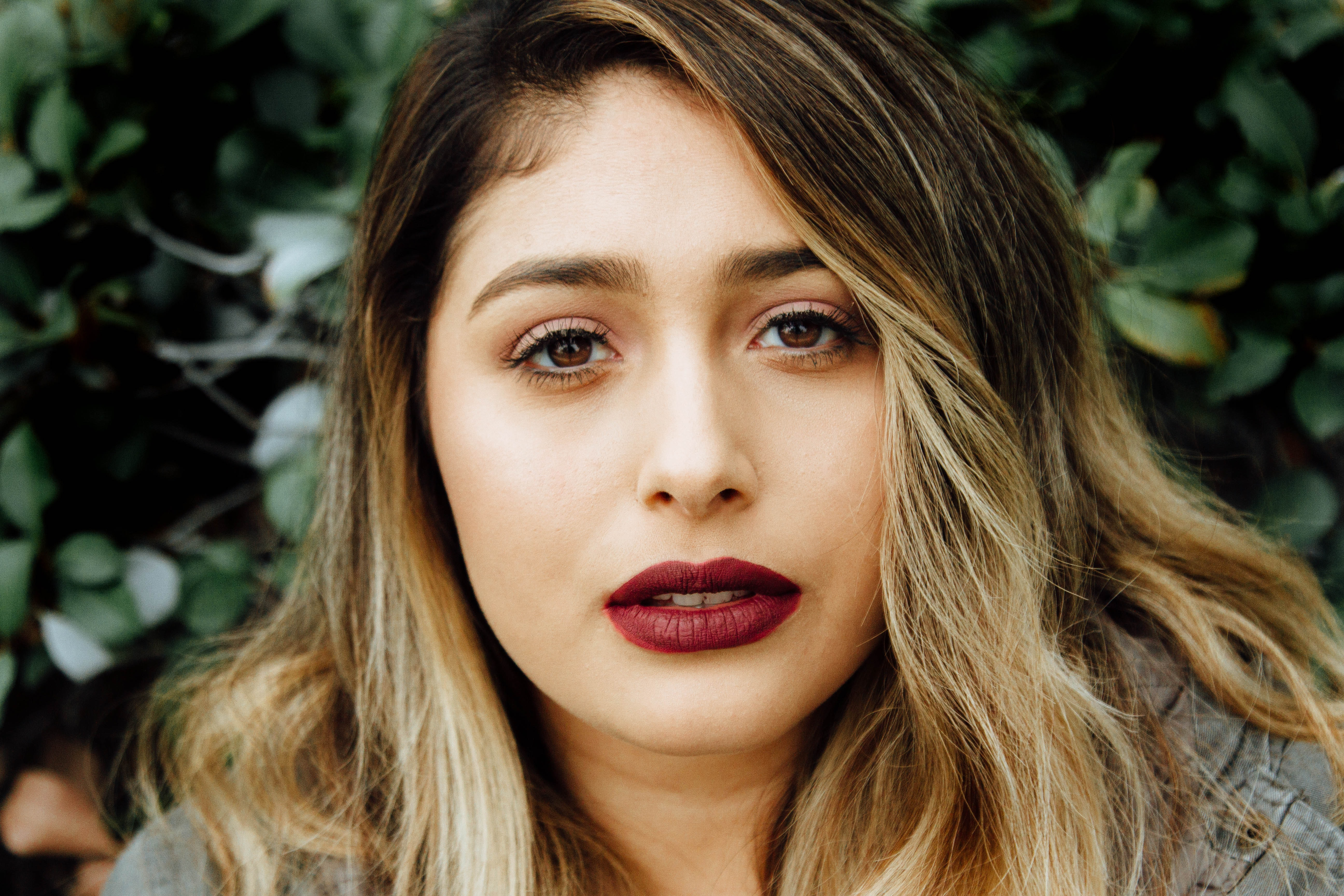 Woman with ombre hair and a bold red lip looking concerned