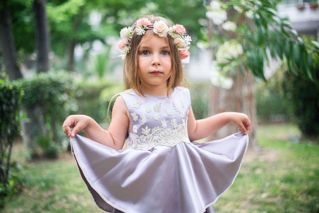 A little girl in a silk dress wearing a floral headband
