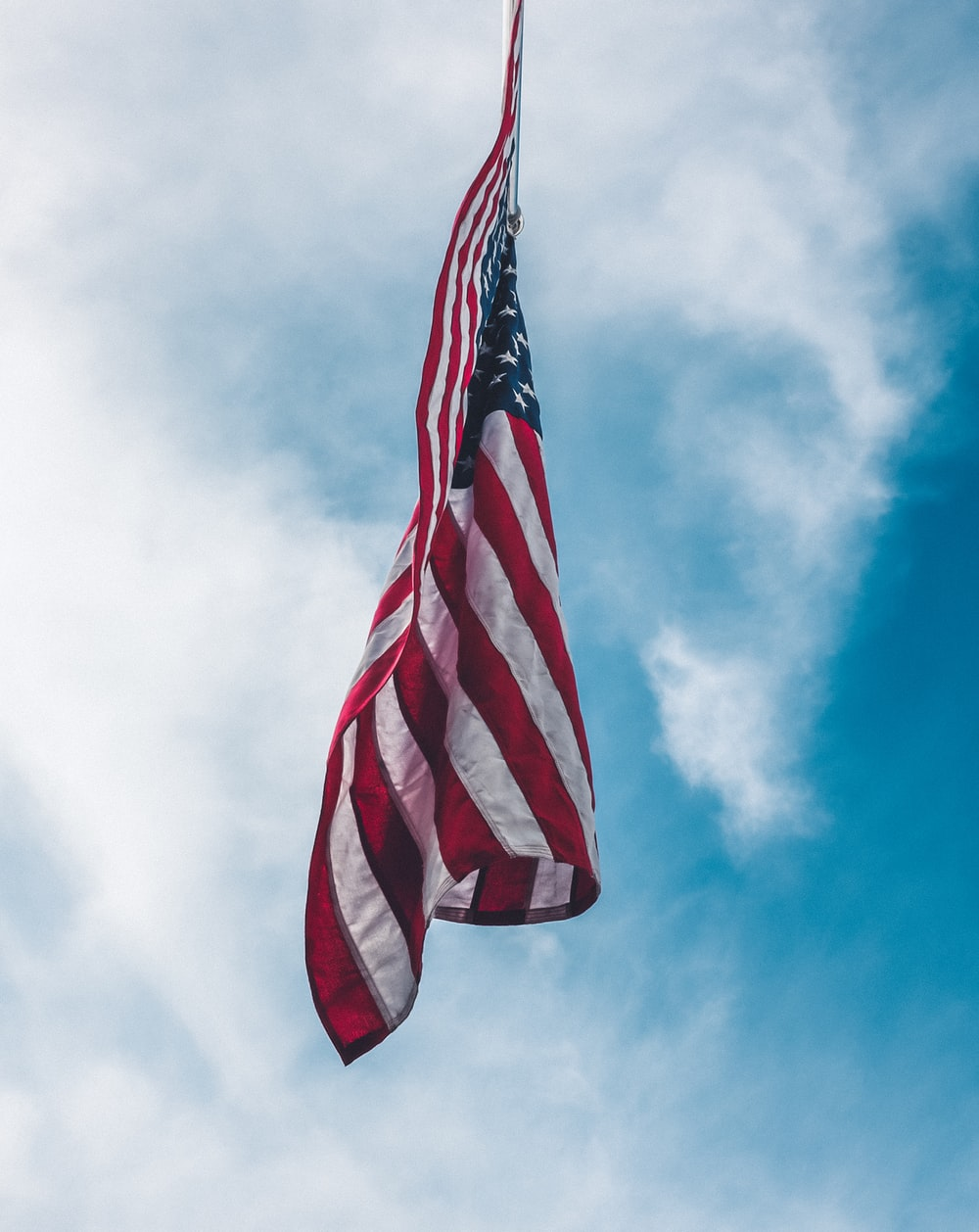 flag of the United State flying under white clouds