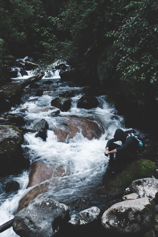 person wearing black hoodie sitting beside waterfalls