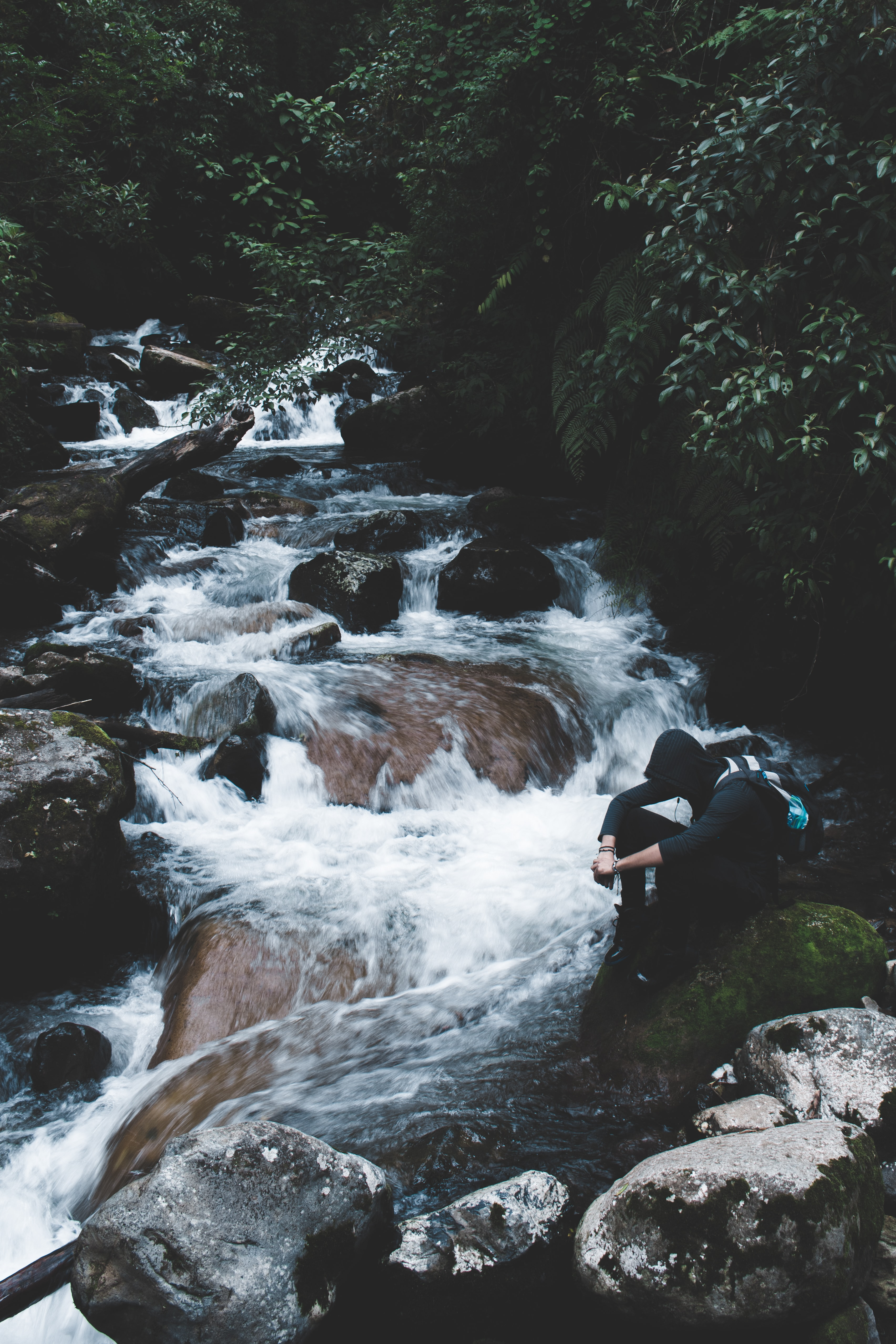 person wearing black hoodie sitting beside waterfalls