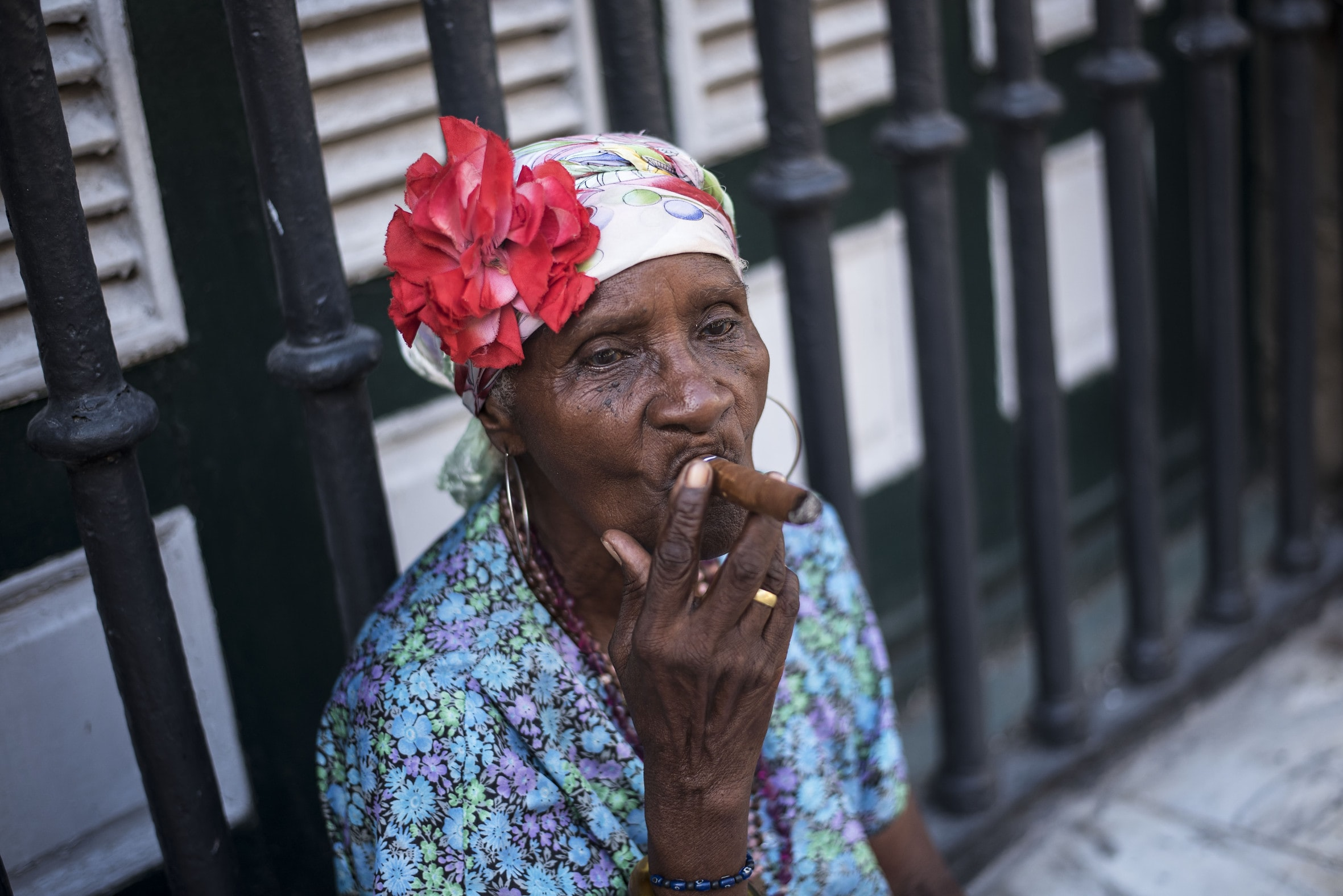 A woman wearing a headscarf with a flower, smoking a cigar