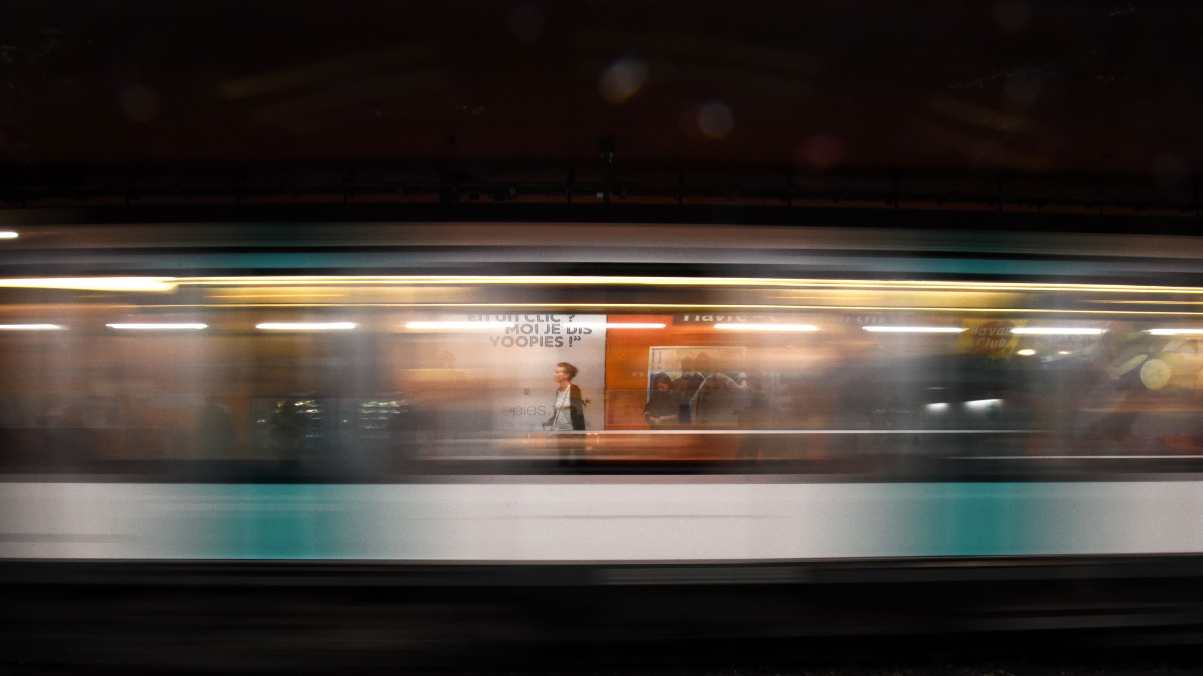 A long-exposure shot of a moving subway train at a platform