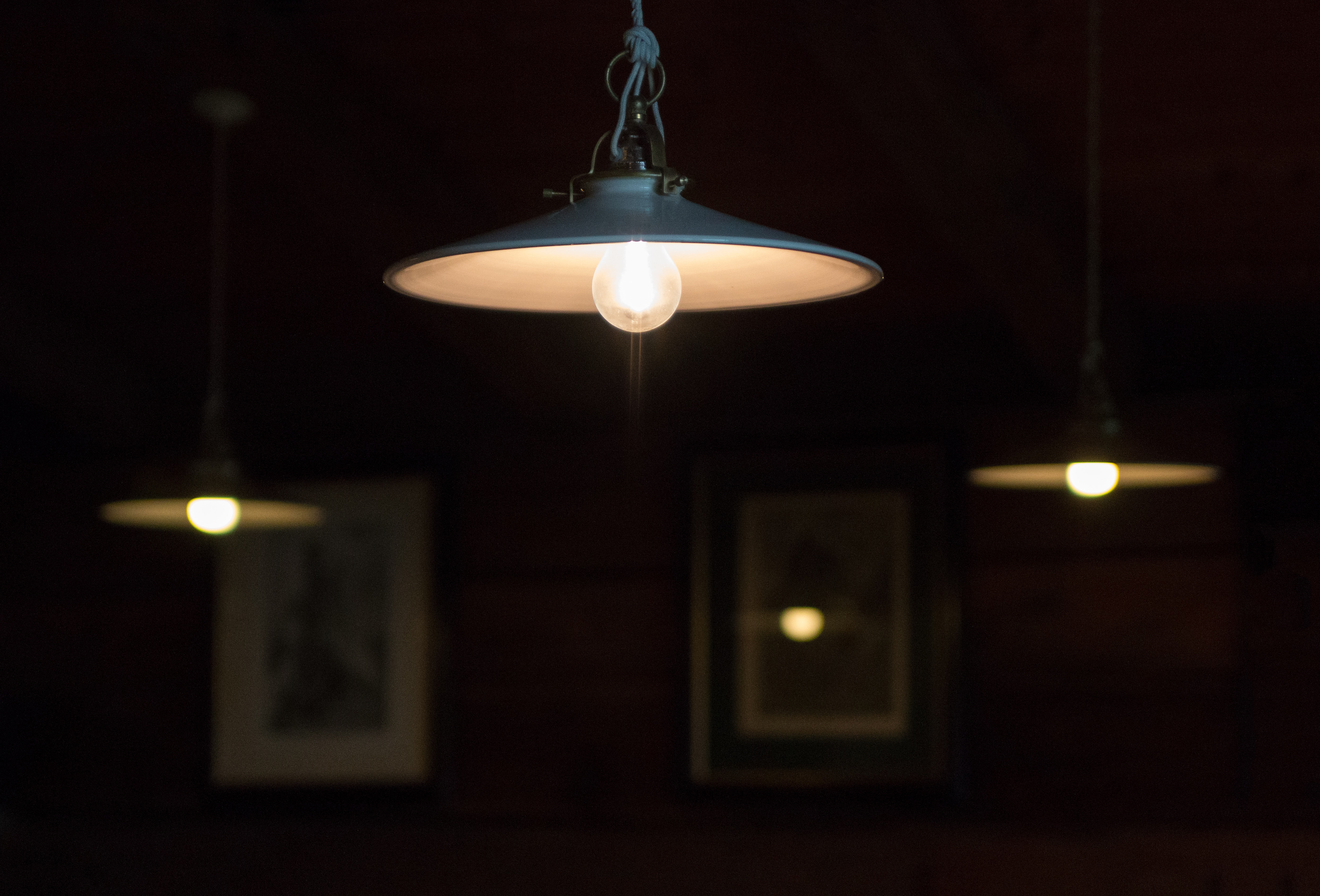 Industrial lamps hang from a ceiling in a living room