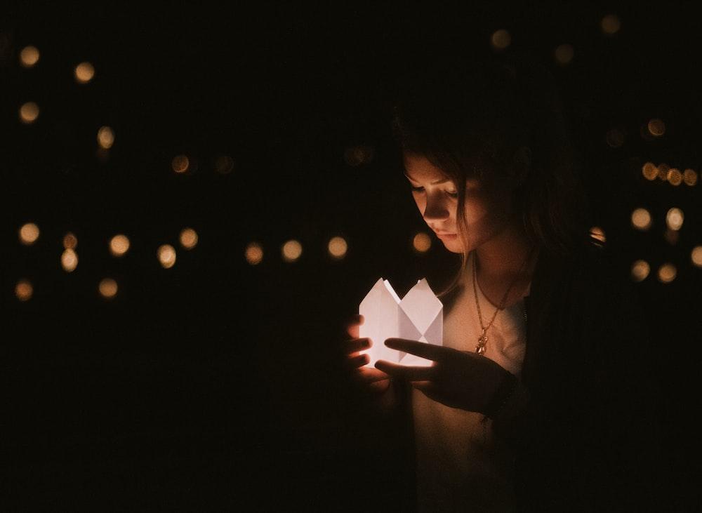 bokeh photography of woman holding paper lantern