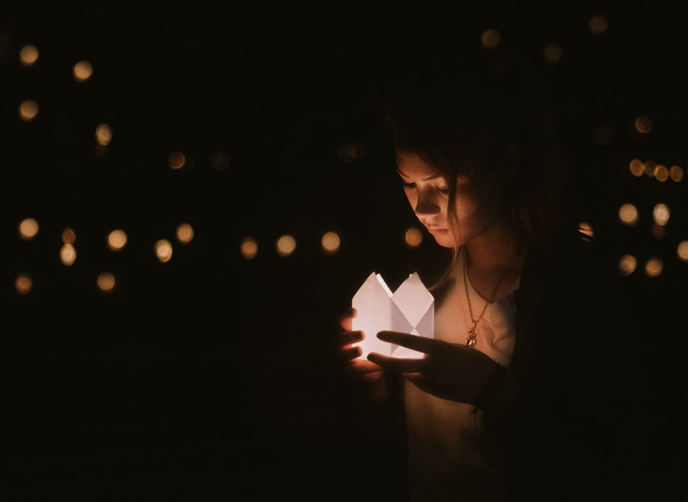 bokeh photography of woman holding paper lantern