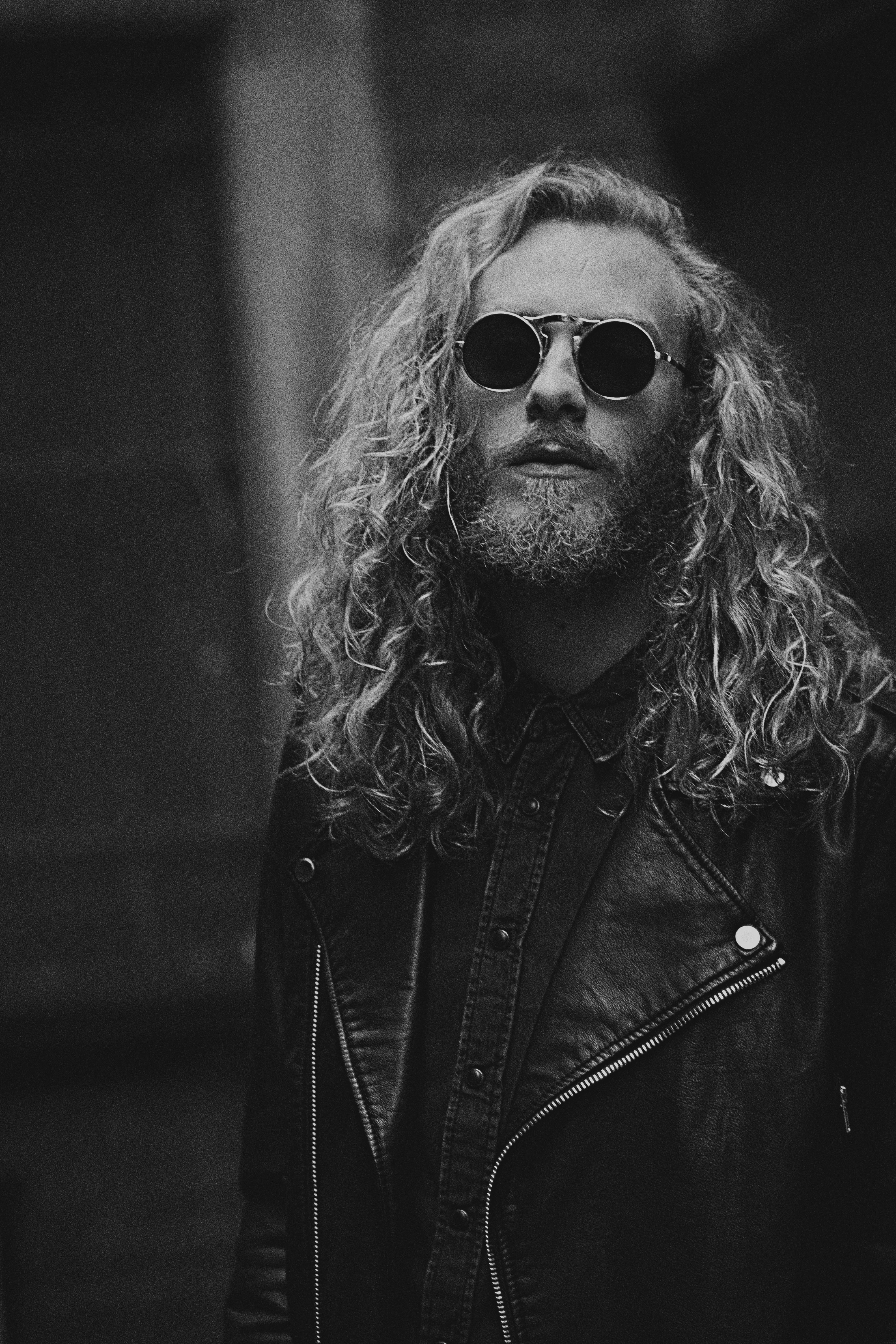 A man with long hair and beard wearing sunglasses and a leather jacket in black and white