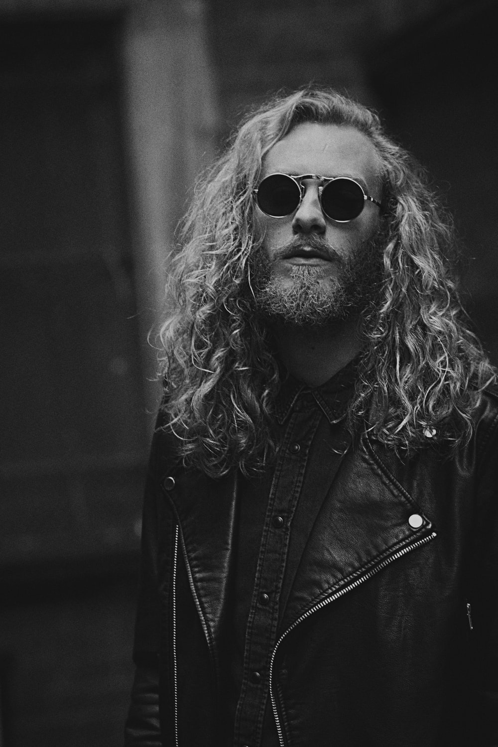 grayscale photo of man in leather jacket