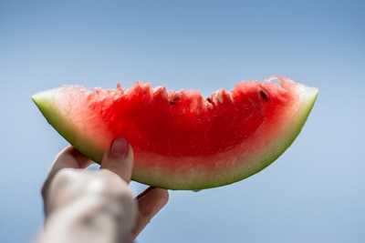 person holding sliced watermelon summertime zoom background
