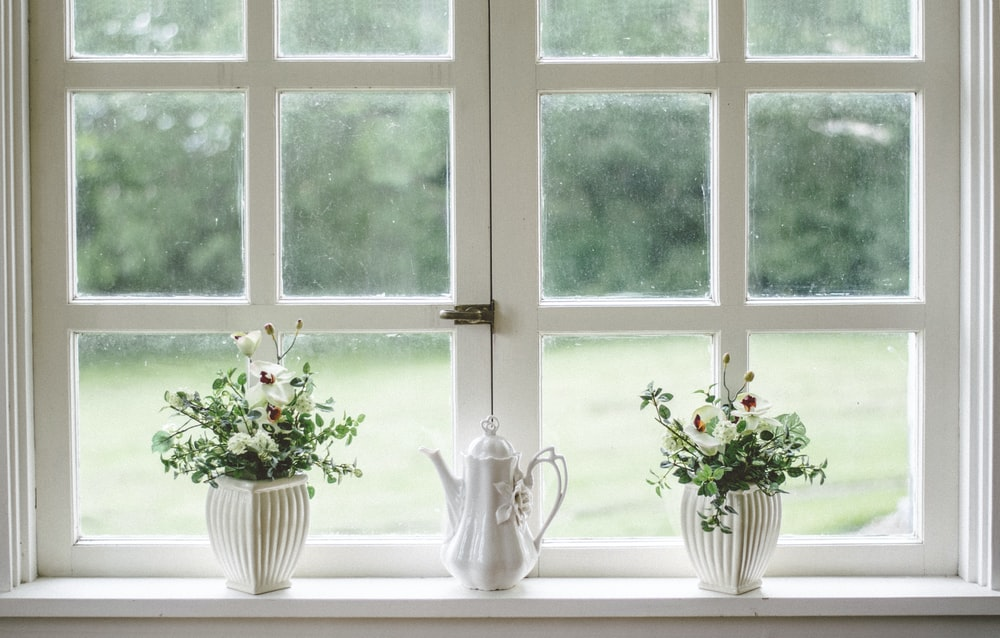 white teapot and tow flower vases on windowpane