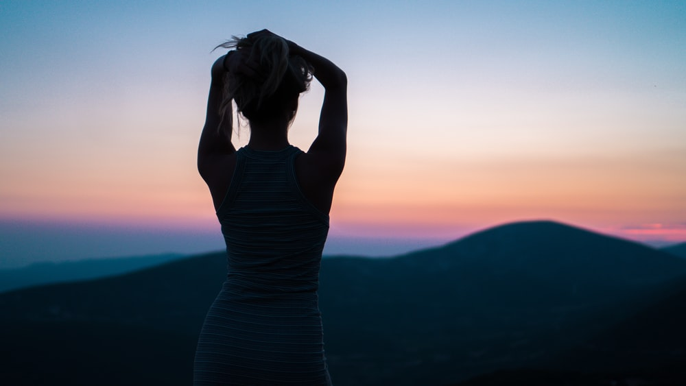 silhouette of woman standing near mountain peak