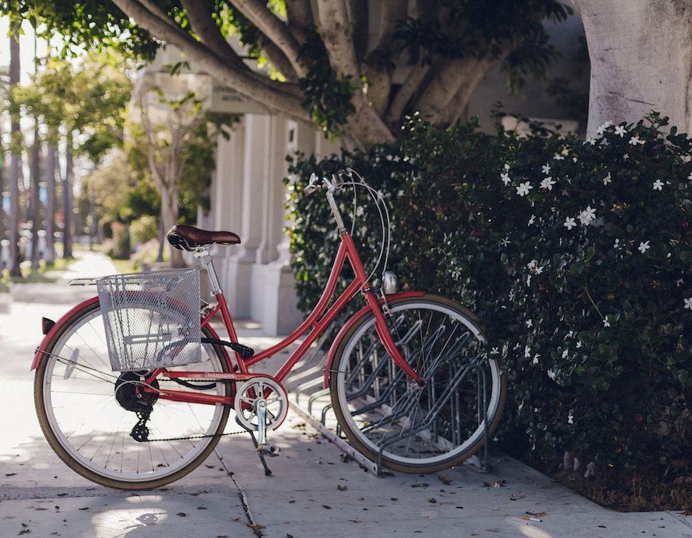 city bike near bush and building at daytime