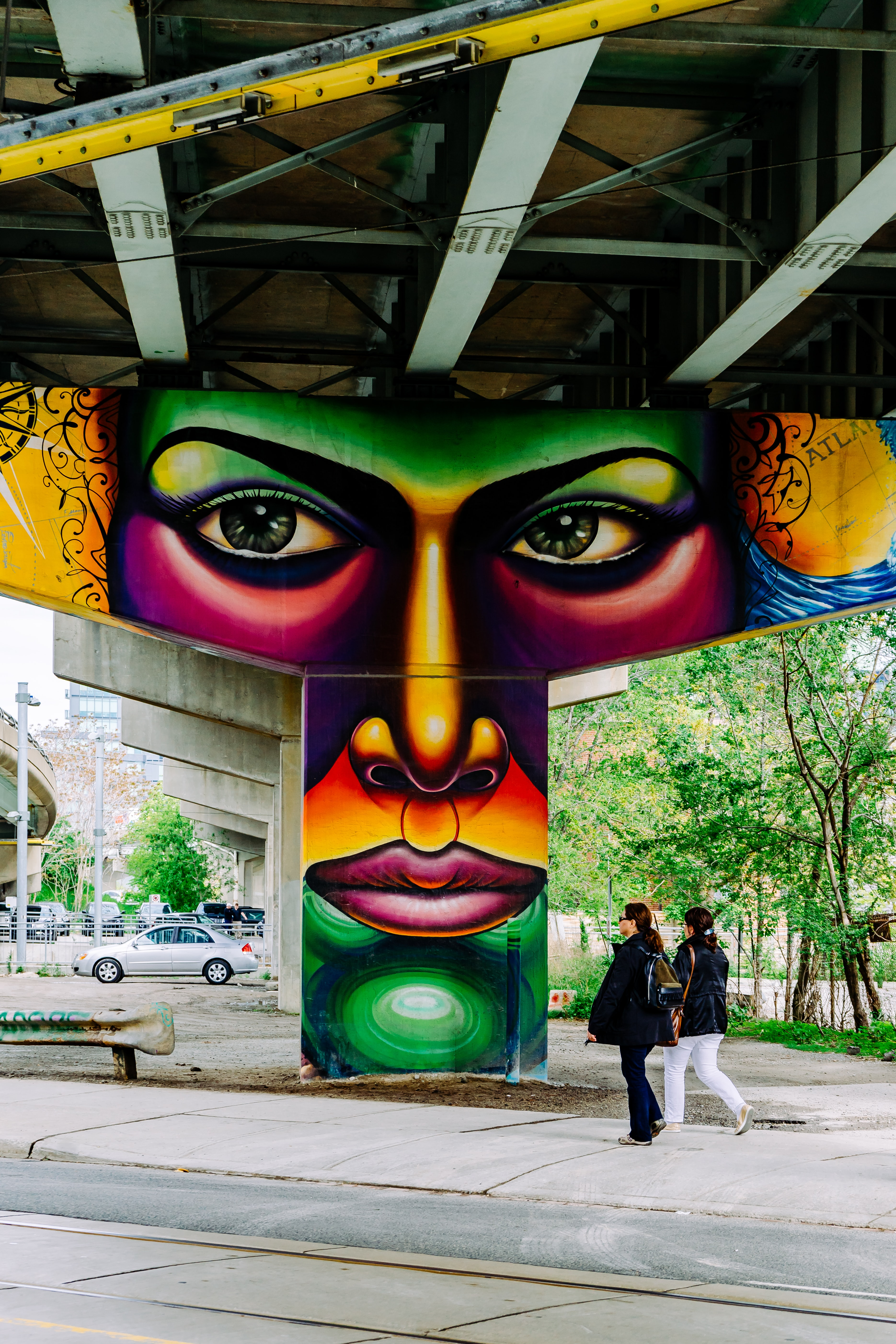 Colorful graffiti of face on bridge structure with people walking on underpass, 507 King St E