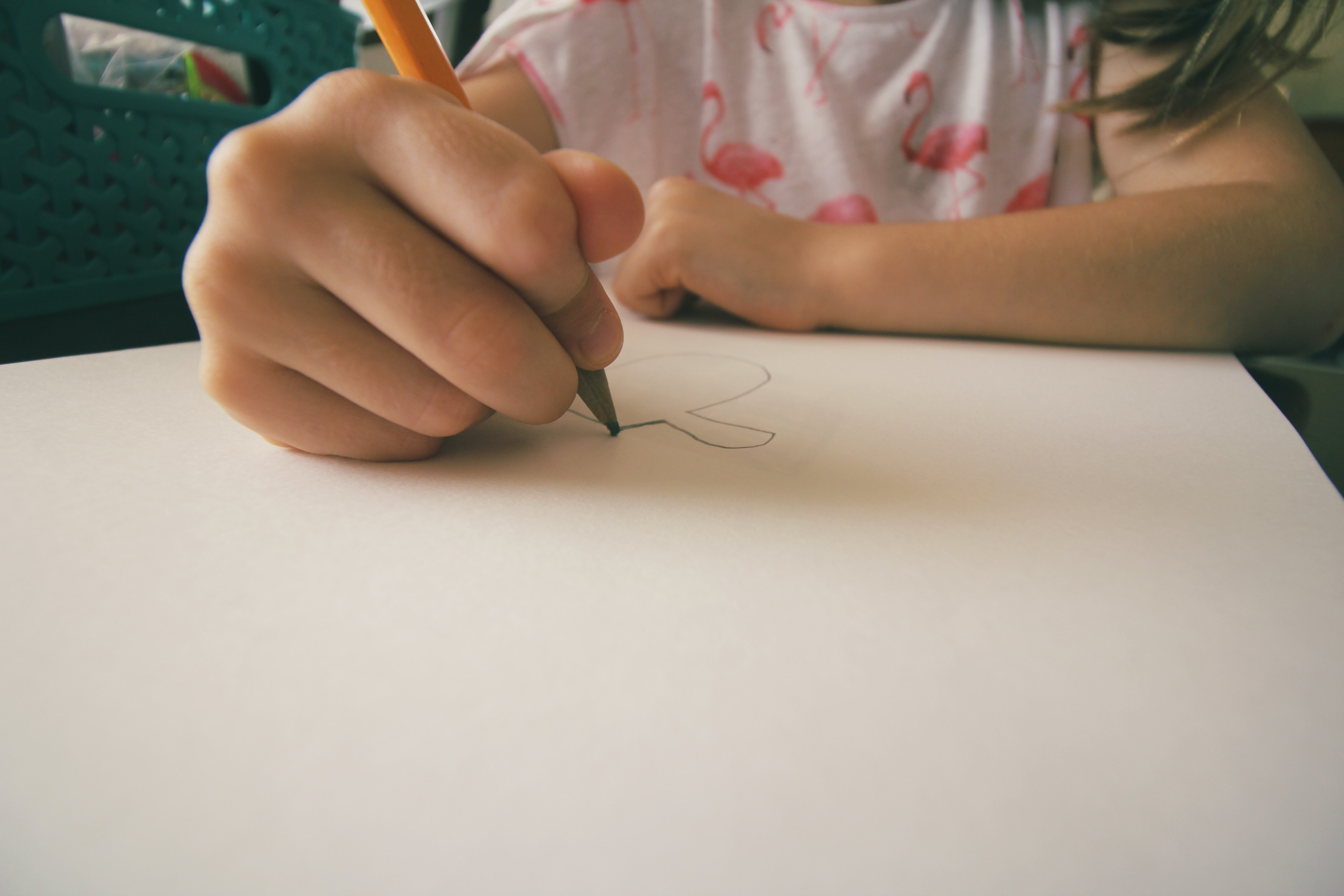 A little girl drawing a picture on paper with a pencil.