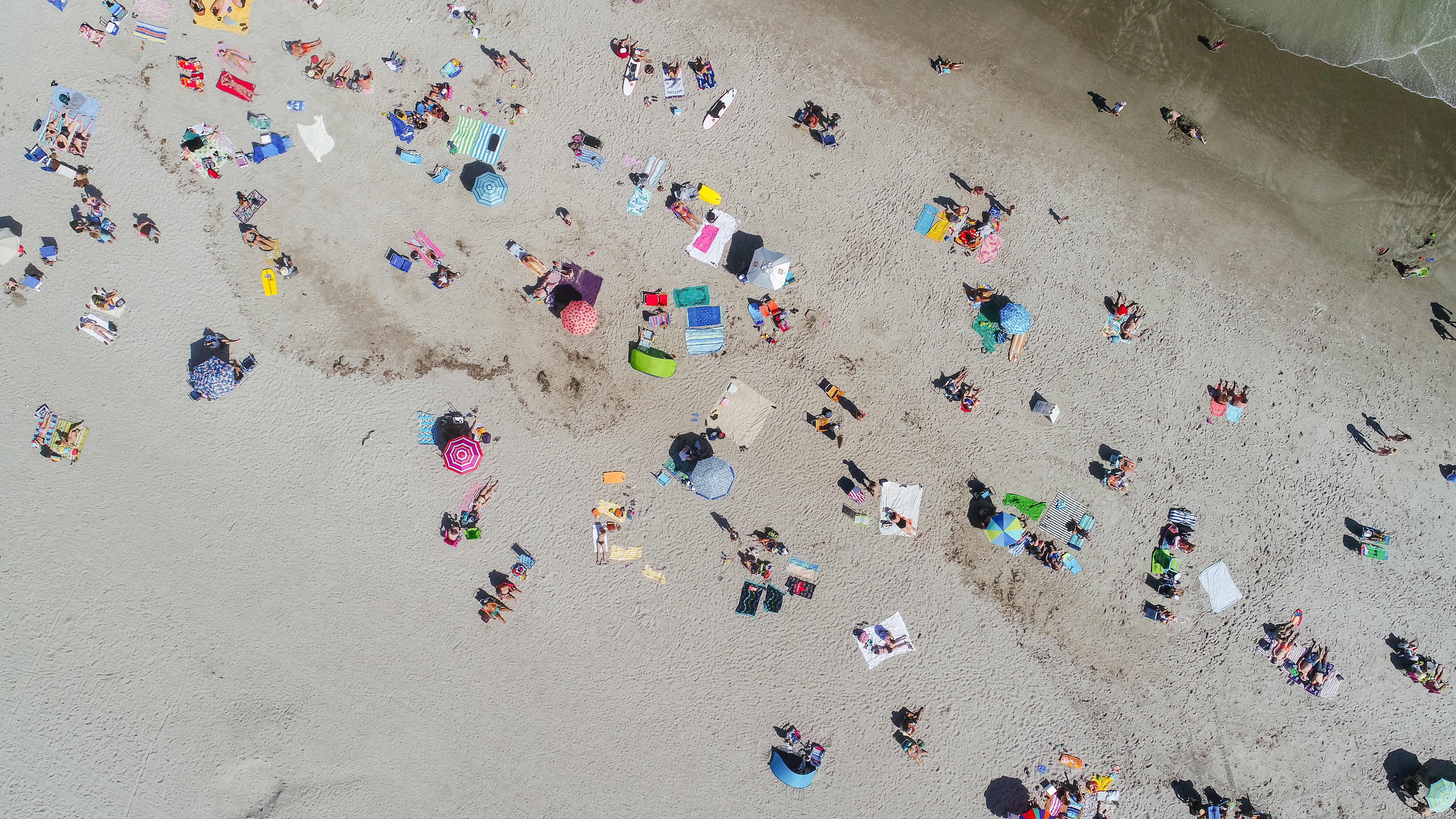 A drone shot of people vacationing on a beach with colorful umbrellas and towels