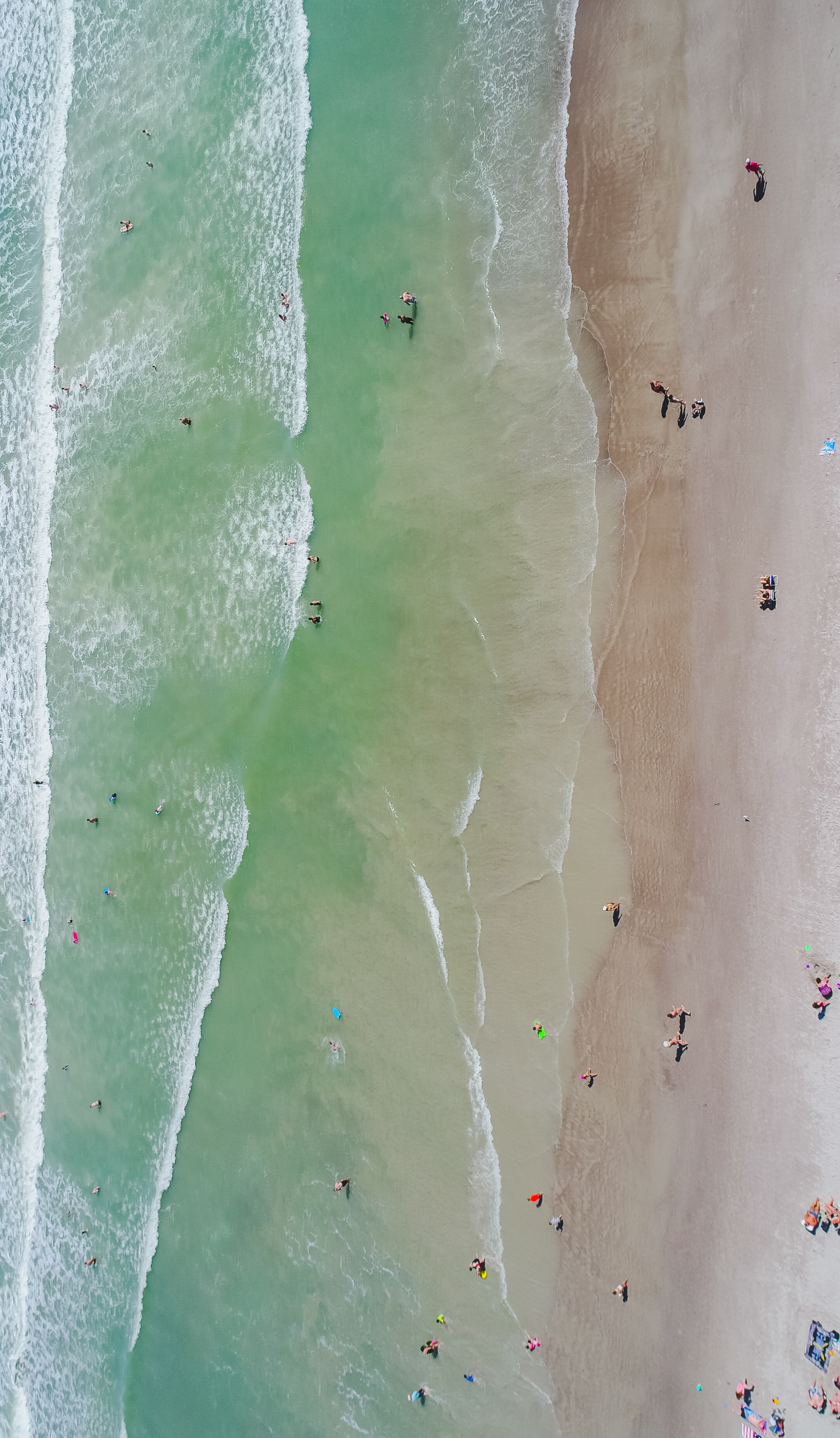 A drone shot of tourists sunbathing on a golden beach and swimming in warm sea water