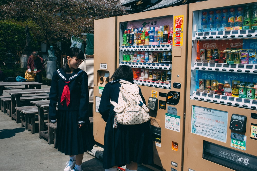 unknown person standing beside vending machine