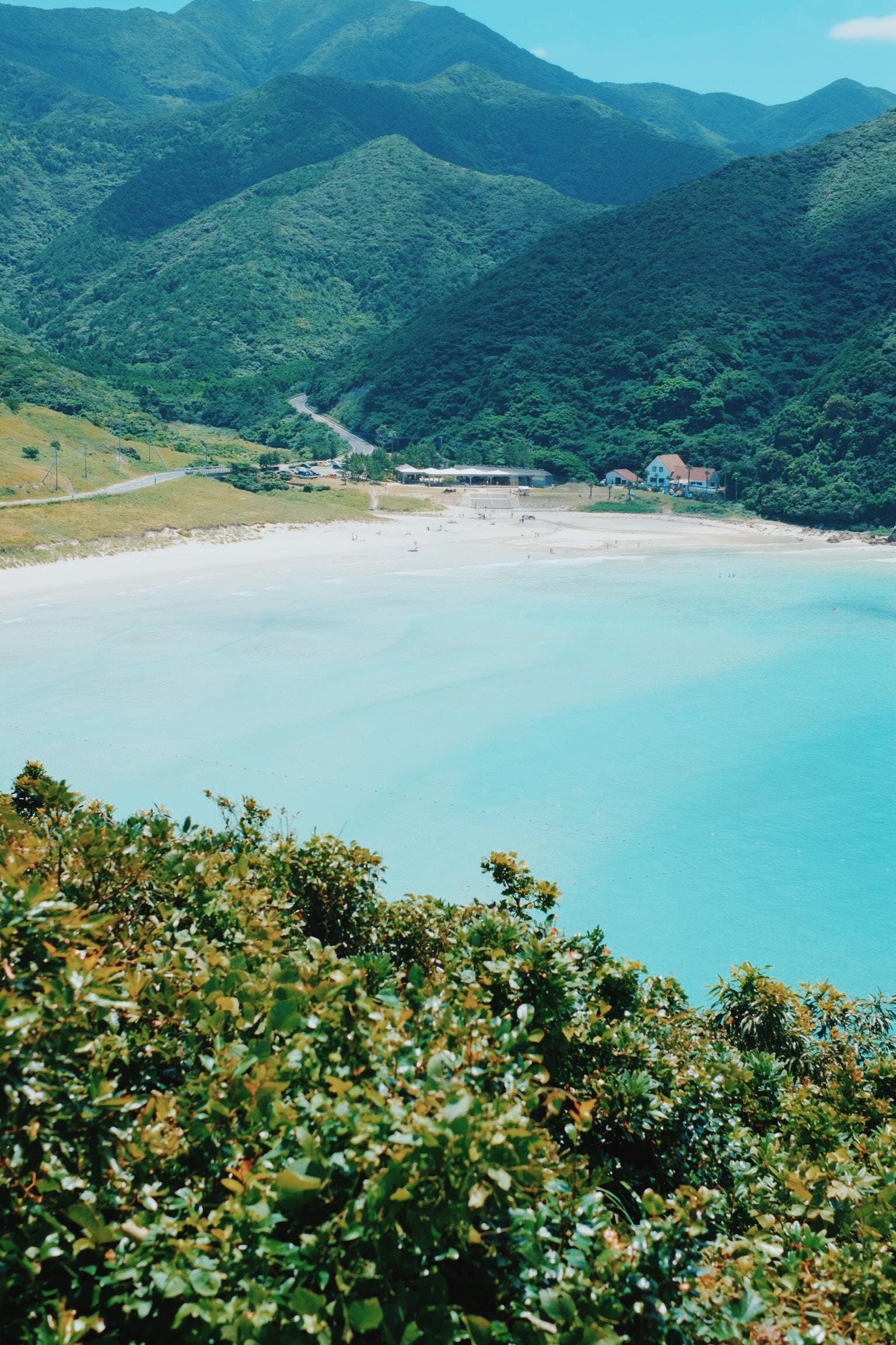 A high shot of a sandy beach in a cove near green hills