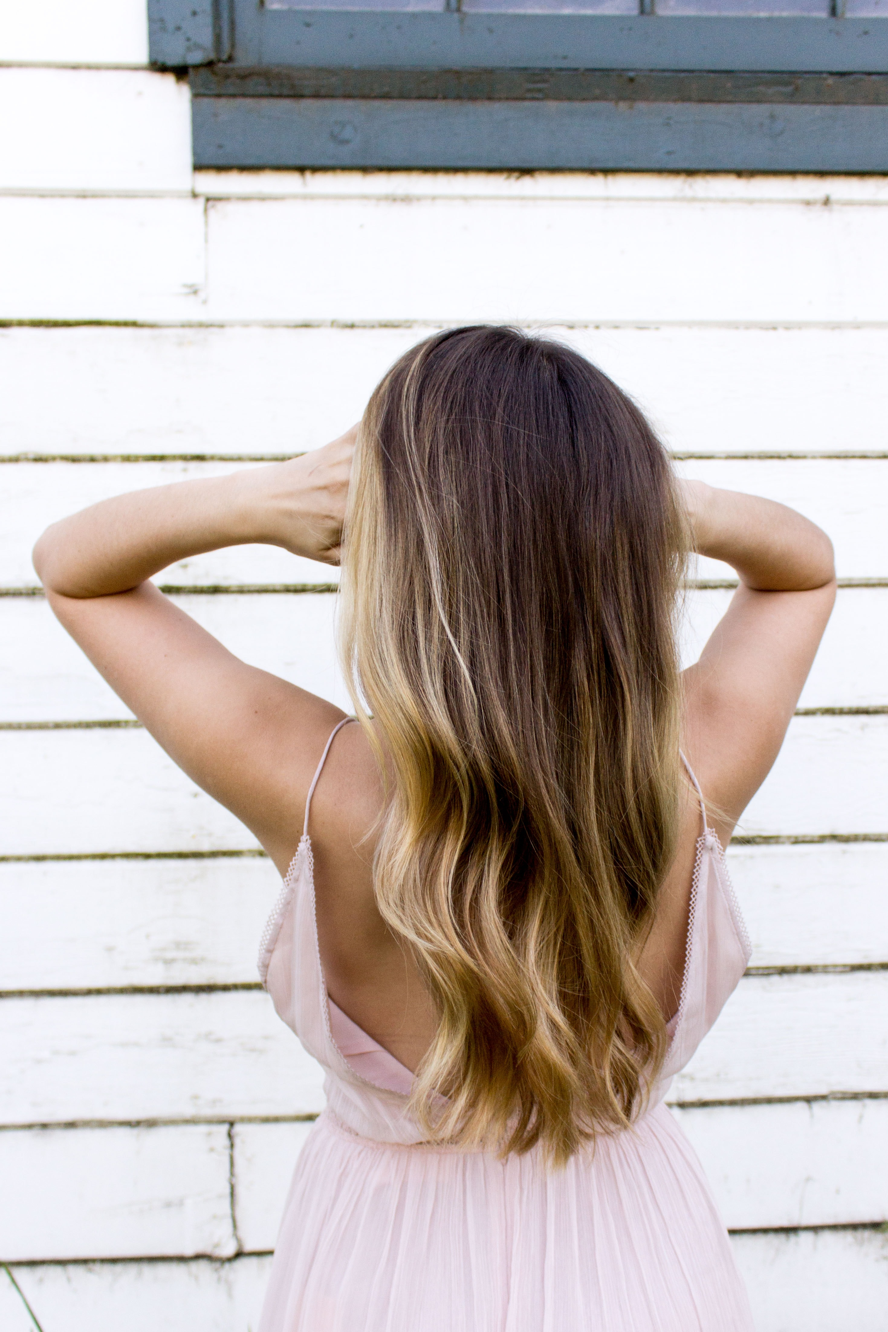 Woman faced away shaking out her hair near a wall