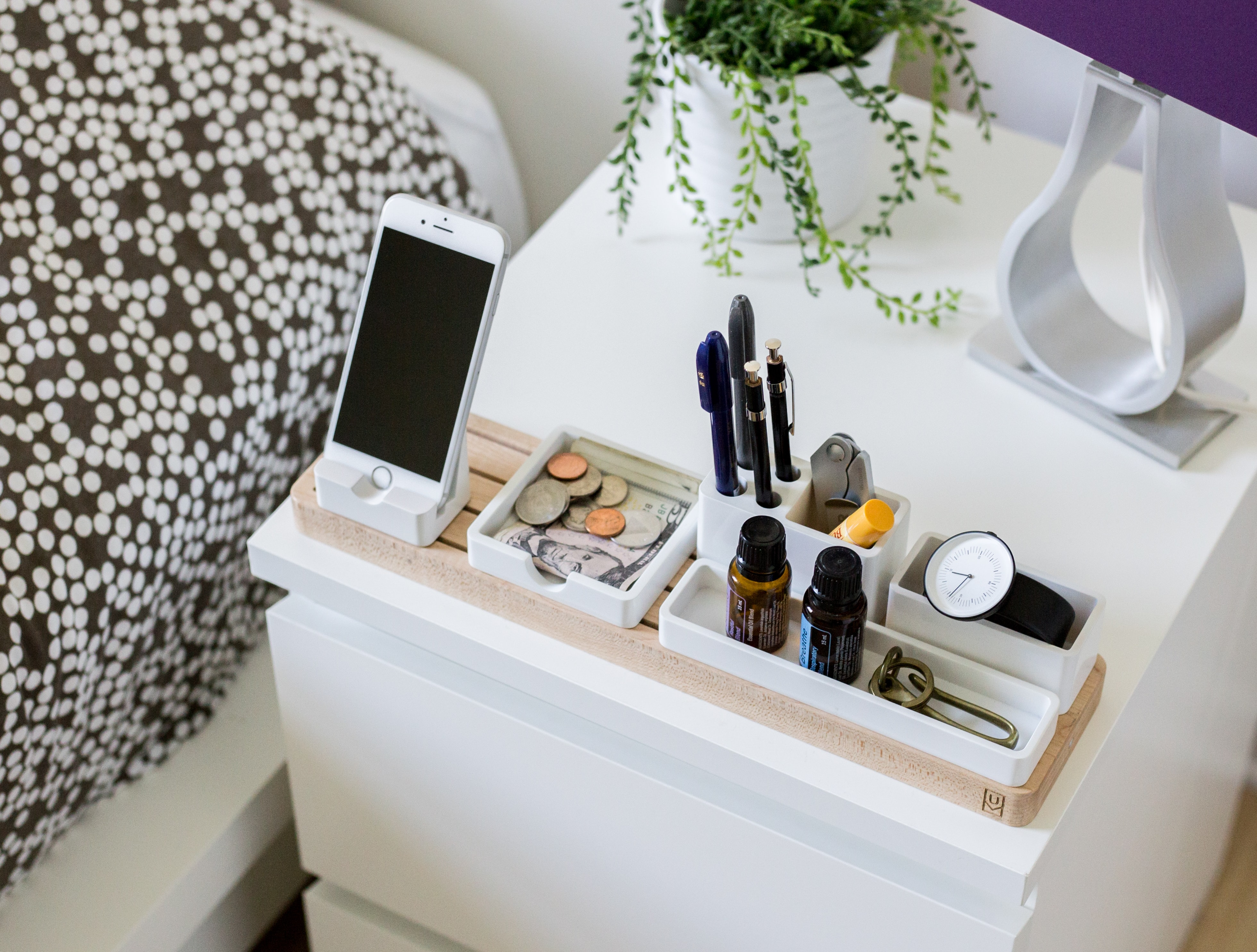 An iPhone, office supplies and a potted plant on a nightstand
