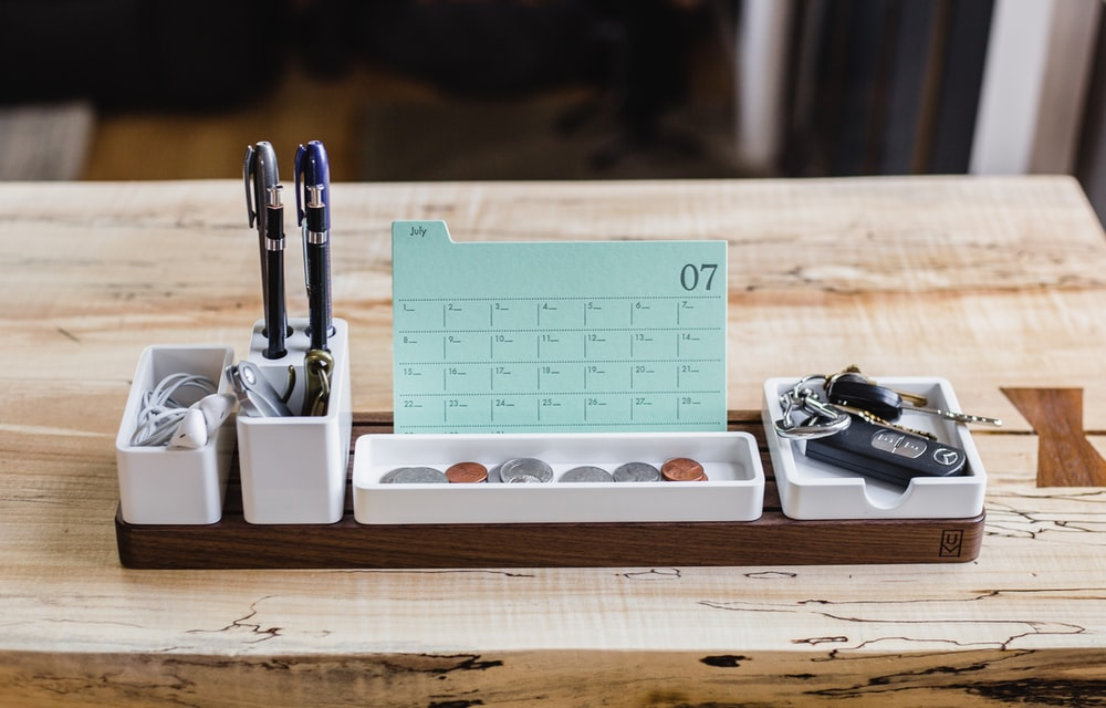coin on tray beside pen organizer on table