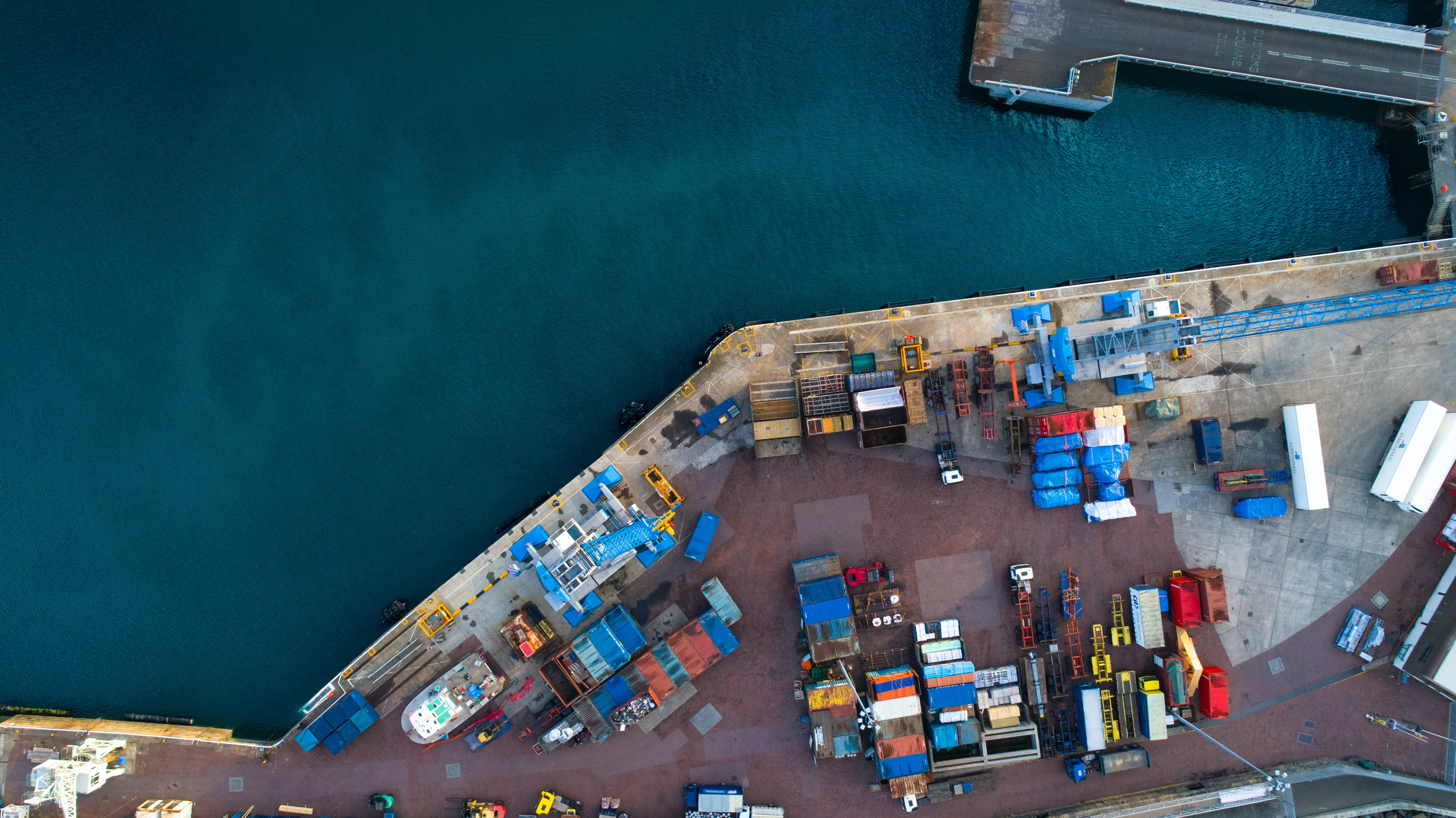 An overhead shot of Saint Peter Port with shipping containers next to the calm sea.
