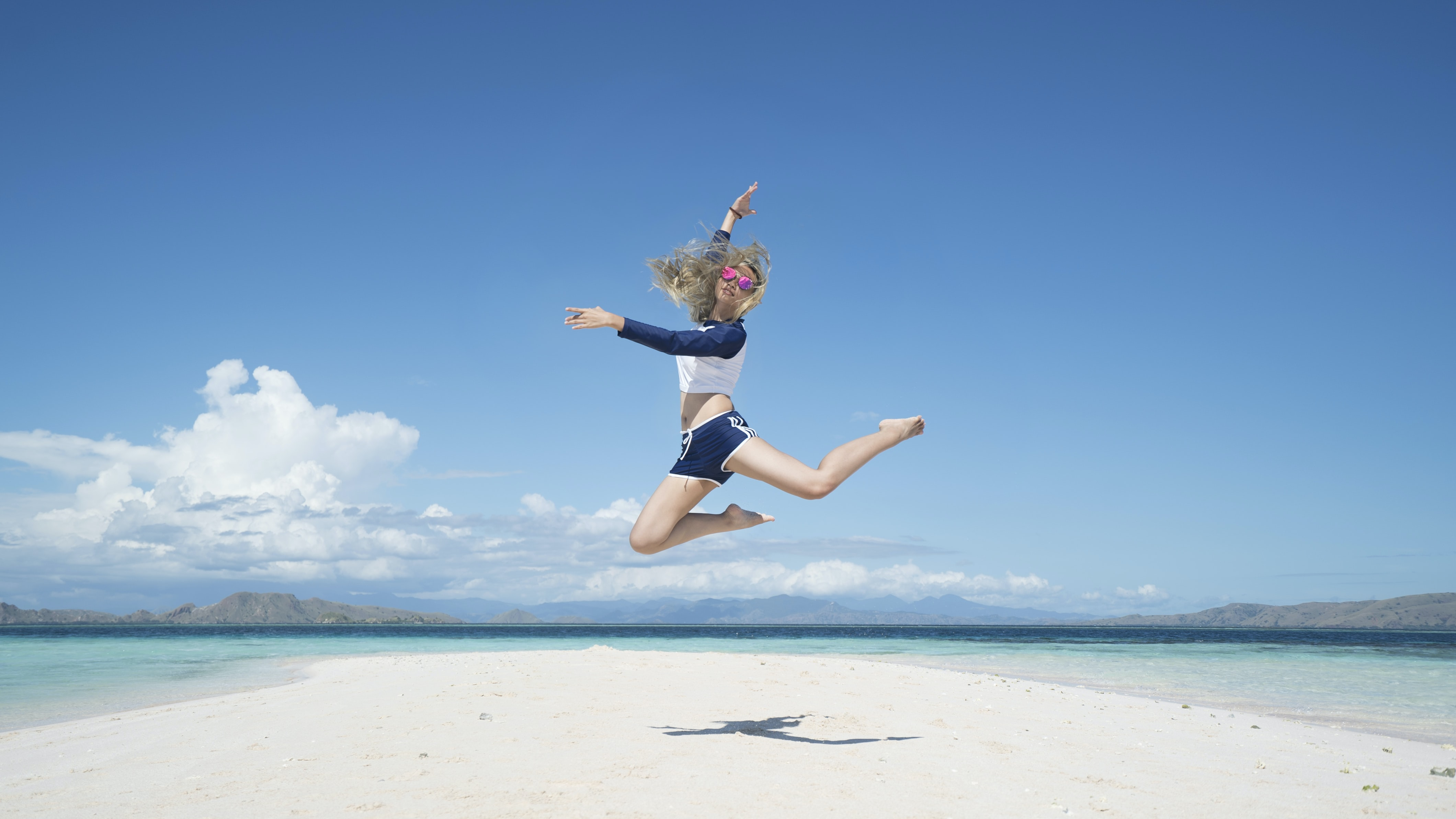 A young woman jumping high above a patch of white sand surrounded by the turquoise sea