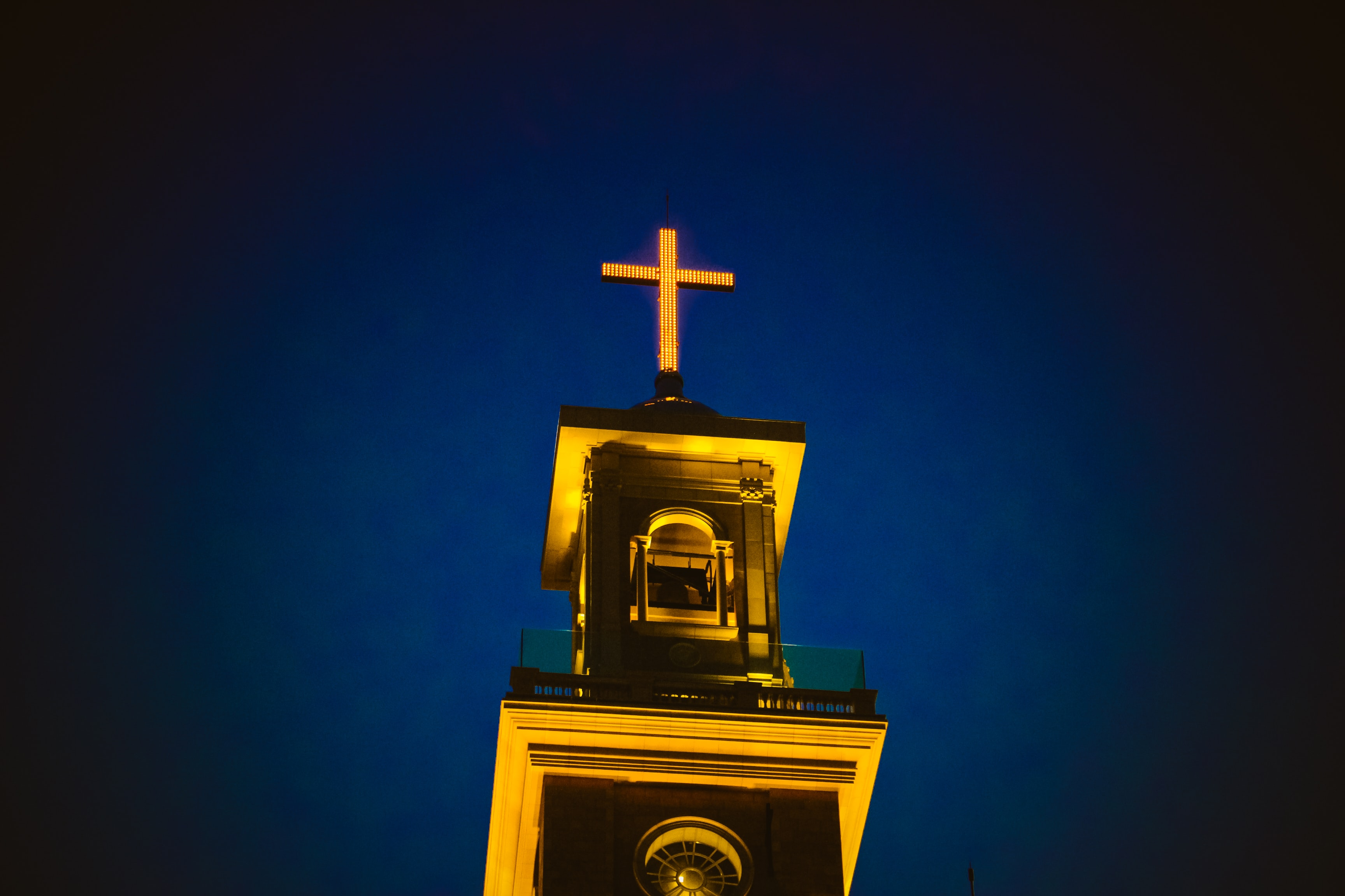 A lighted church steeple and cross against the dark blue night sky in Beirut.