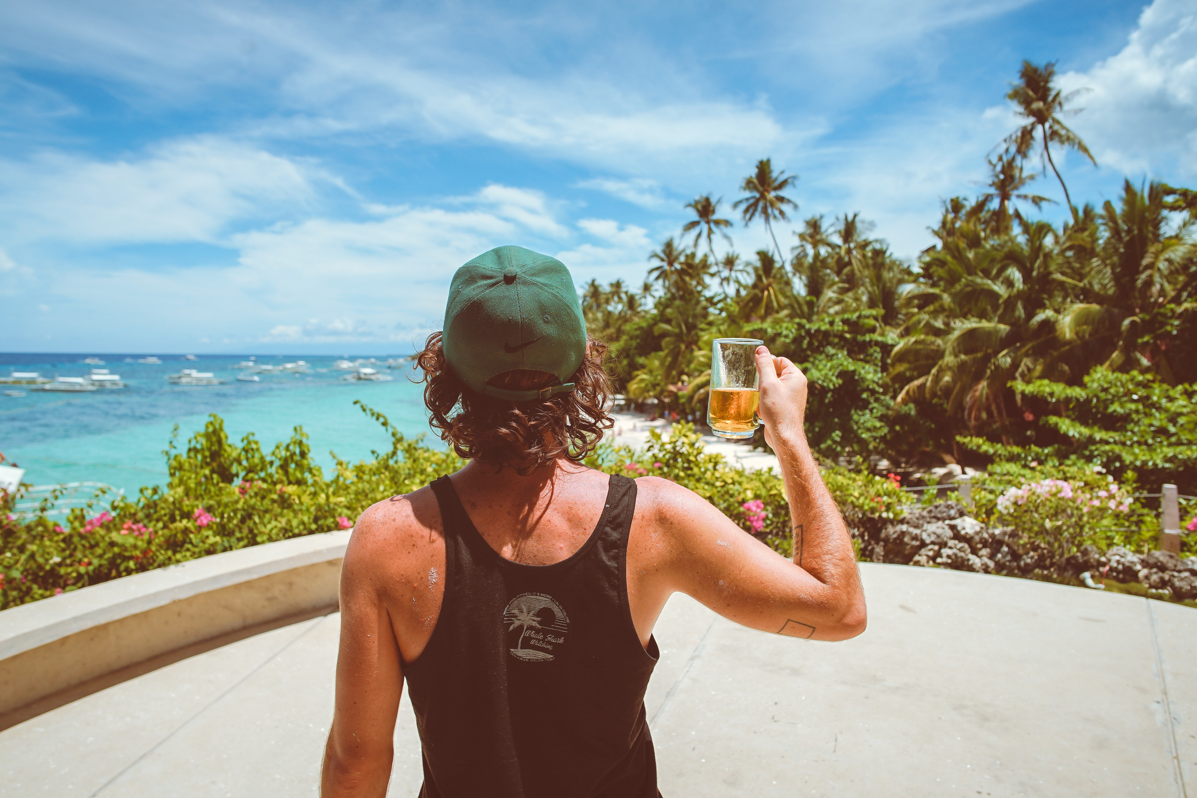 man in black tank top holding clear drinking glass