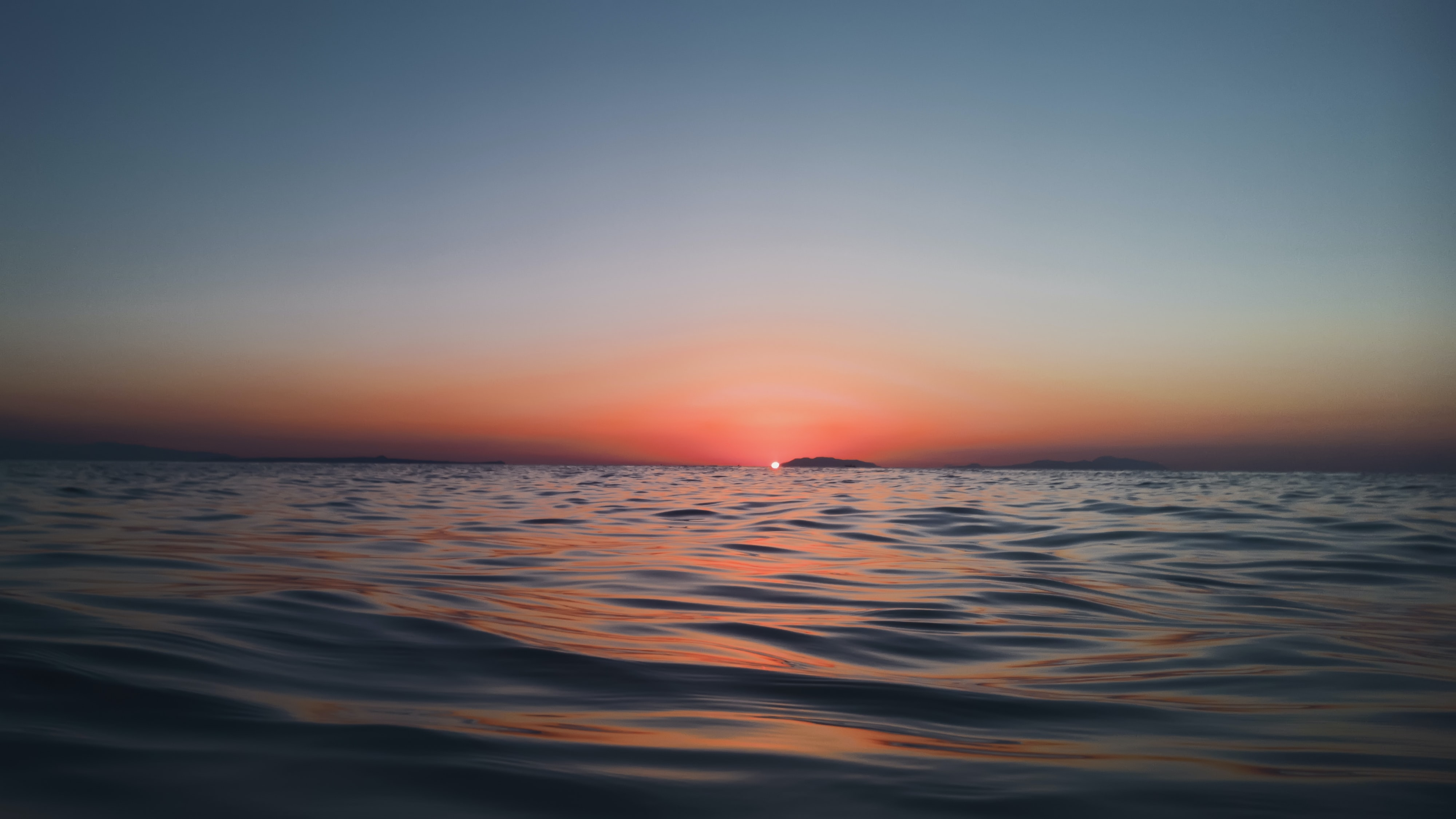 A water-level shot looking toward a horizon of low-lying lands in Messina, Italy during dawn-or-dusk sunset, turning the sky pink, though fades to blue