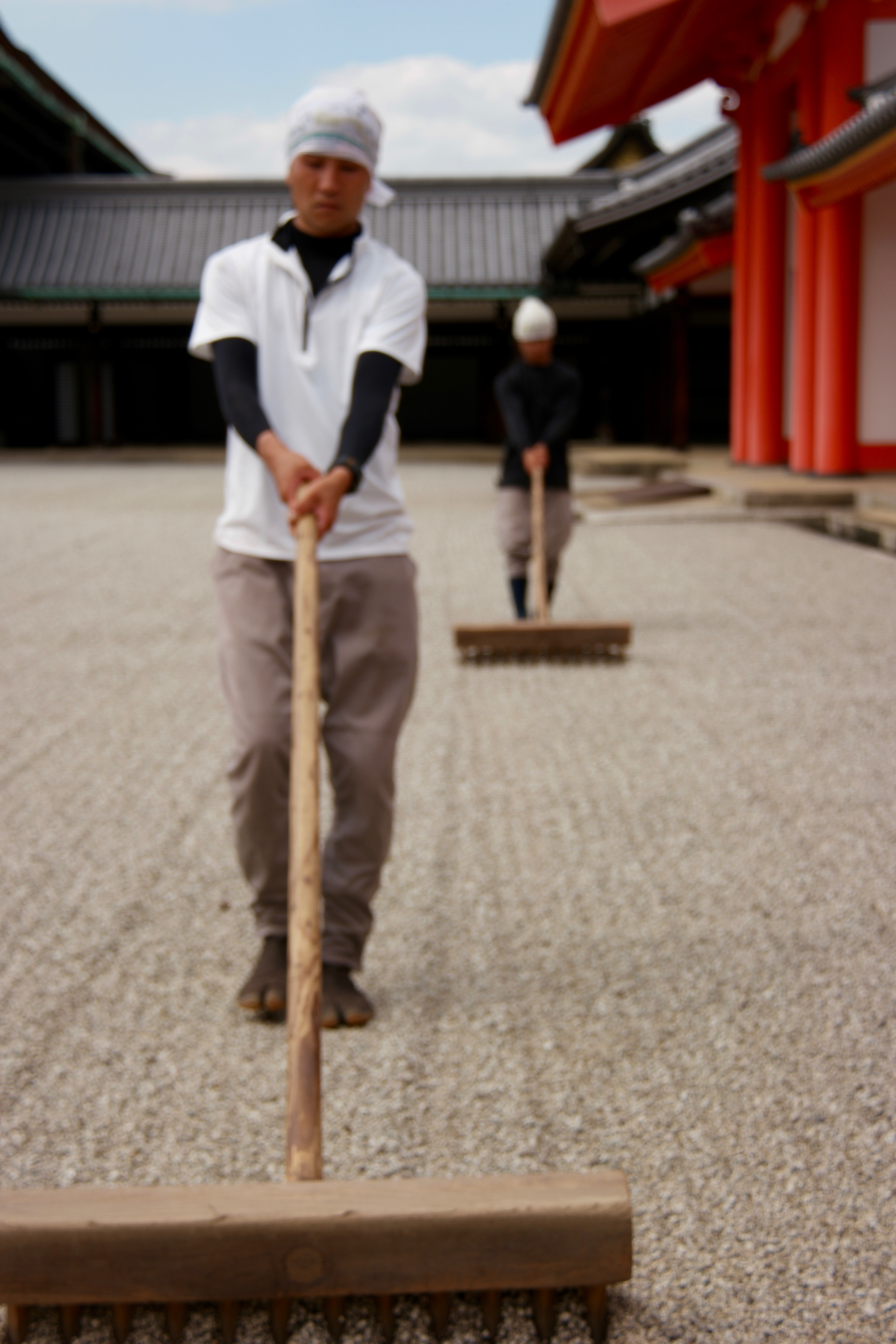 Two Asian men sweeping at their temple's courtyard.