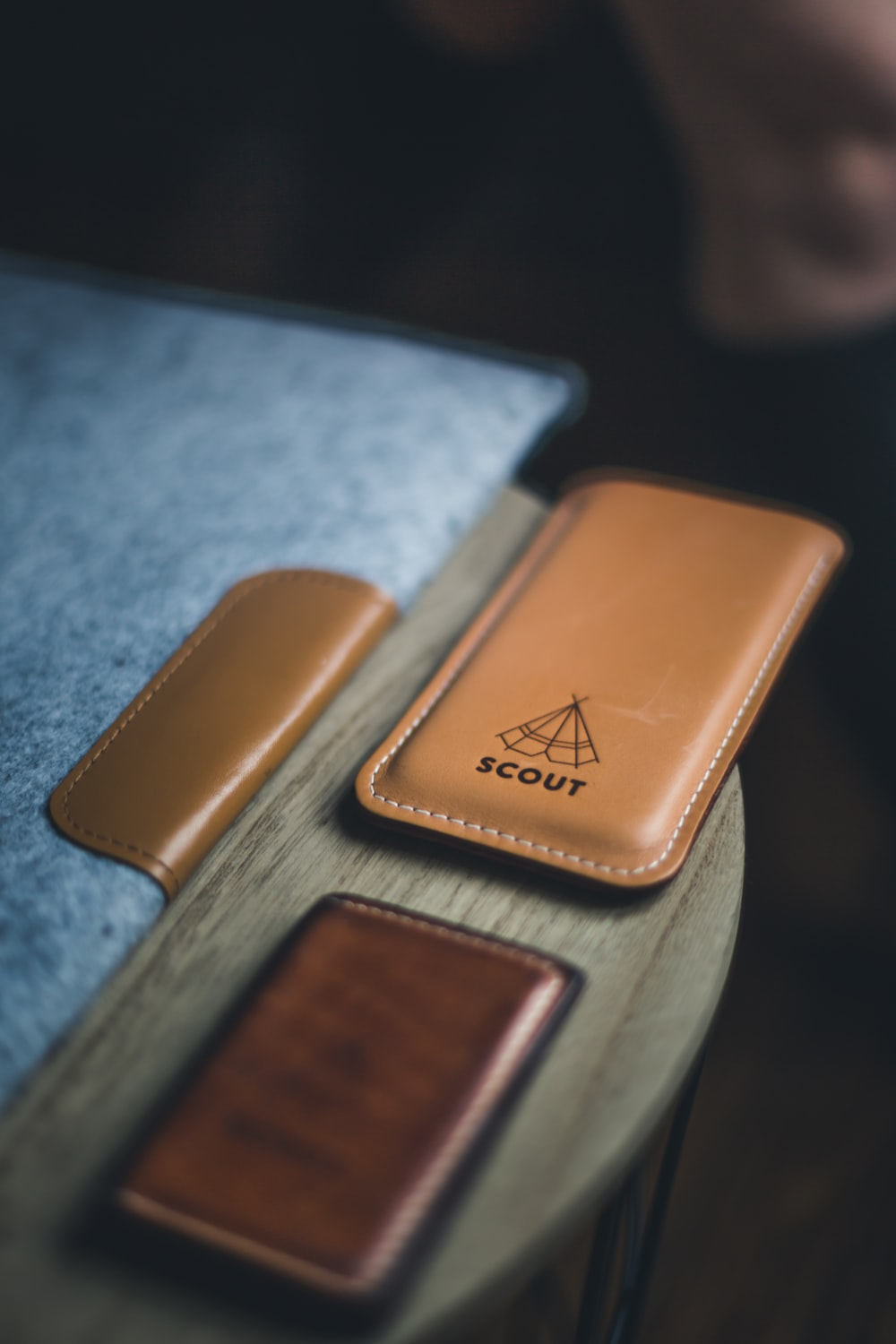 "Leather laptop cover, wallet, and phone holder with a label that reads ""SCOUT"" on a wooden circular table"