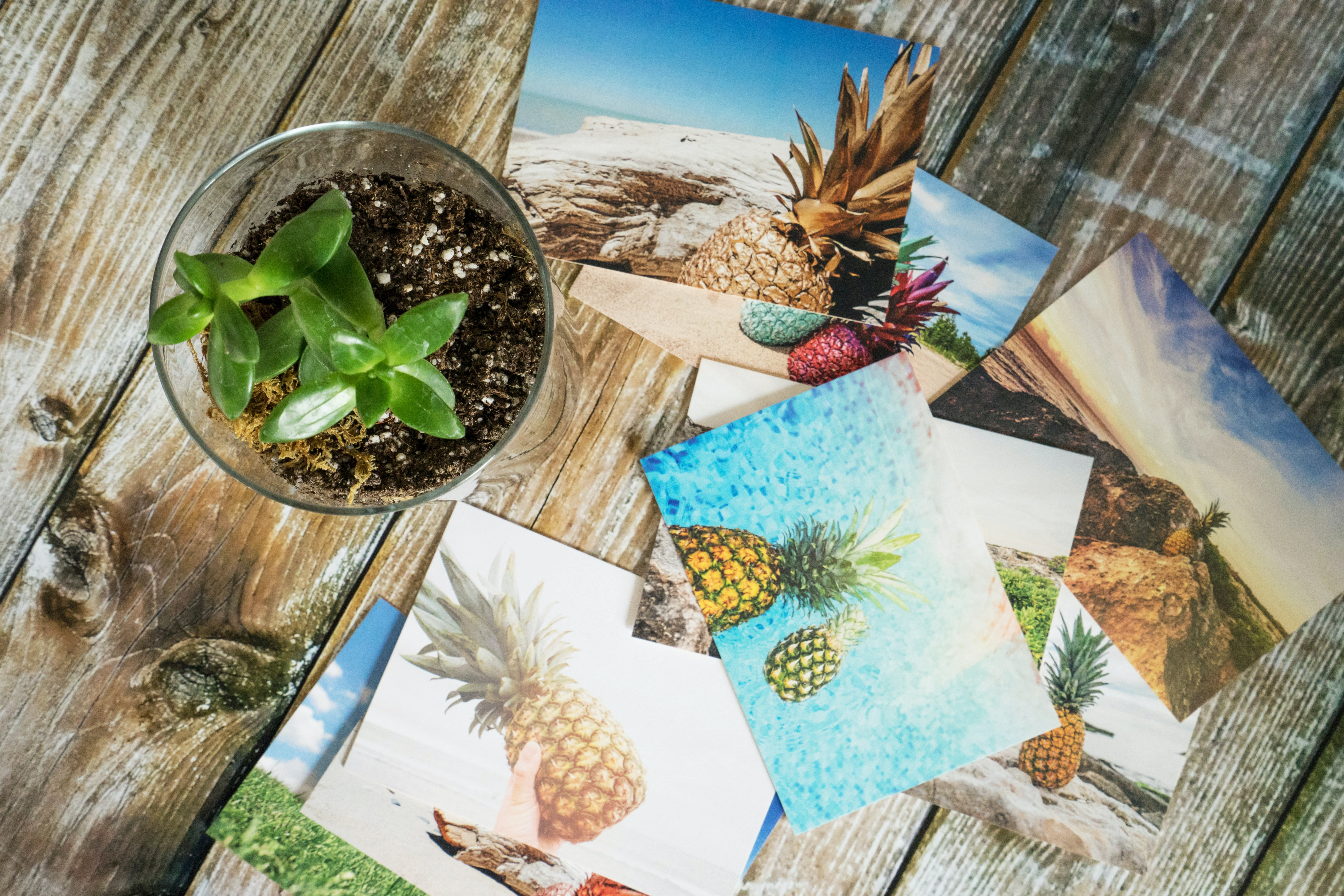 Scattered photo prints on a wooden table.