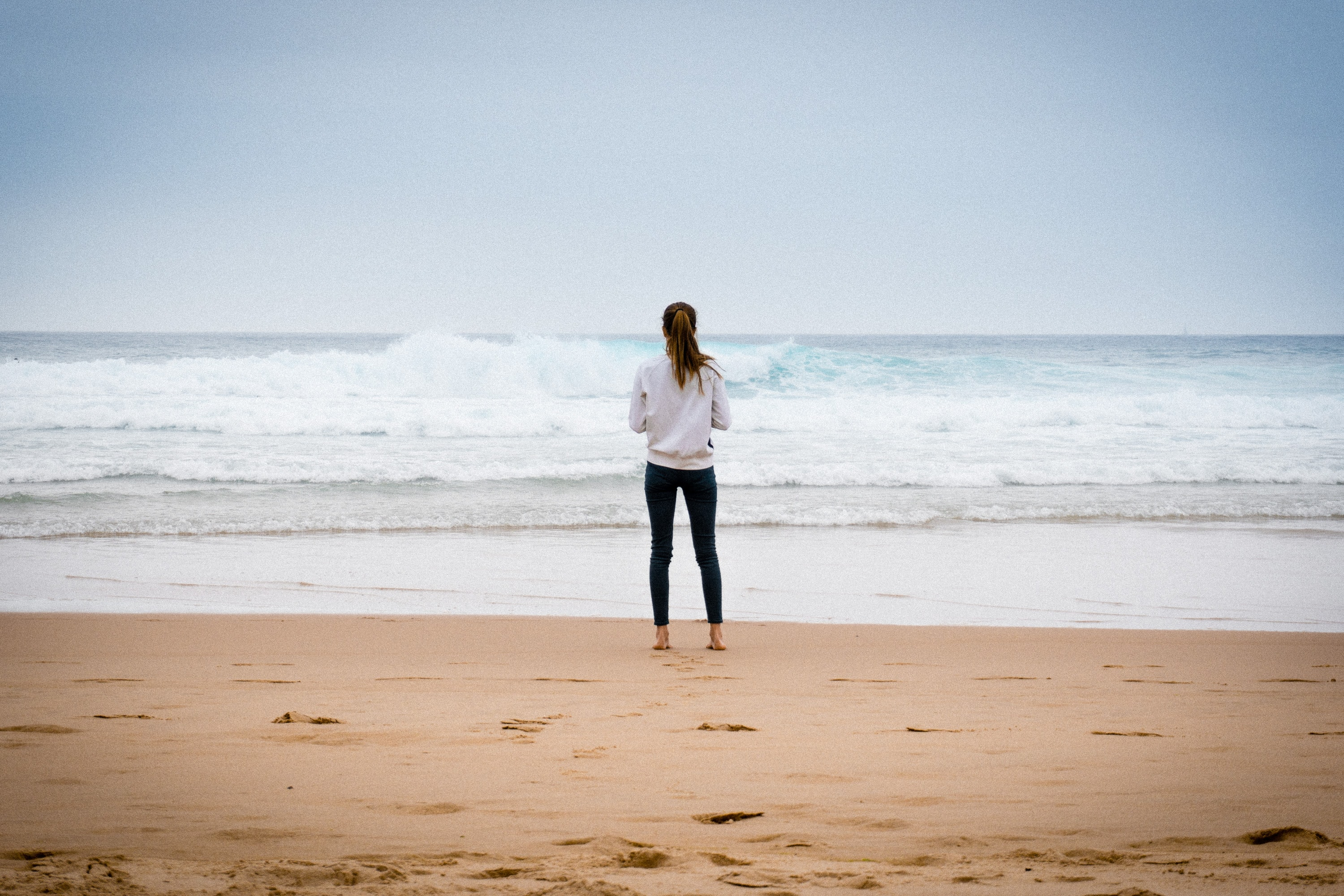 A woman standing at the water of Guincho Beach looking at the incoming waves