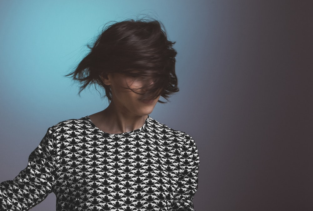 Woman wearing a patterned sweater flips her short hair in front of her face