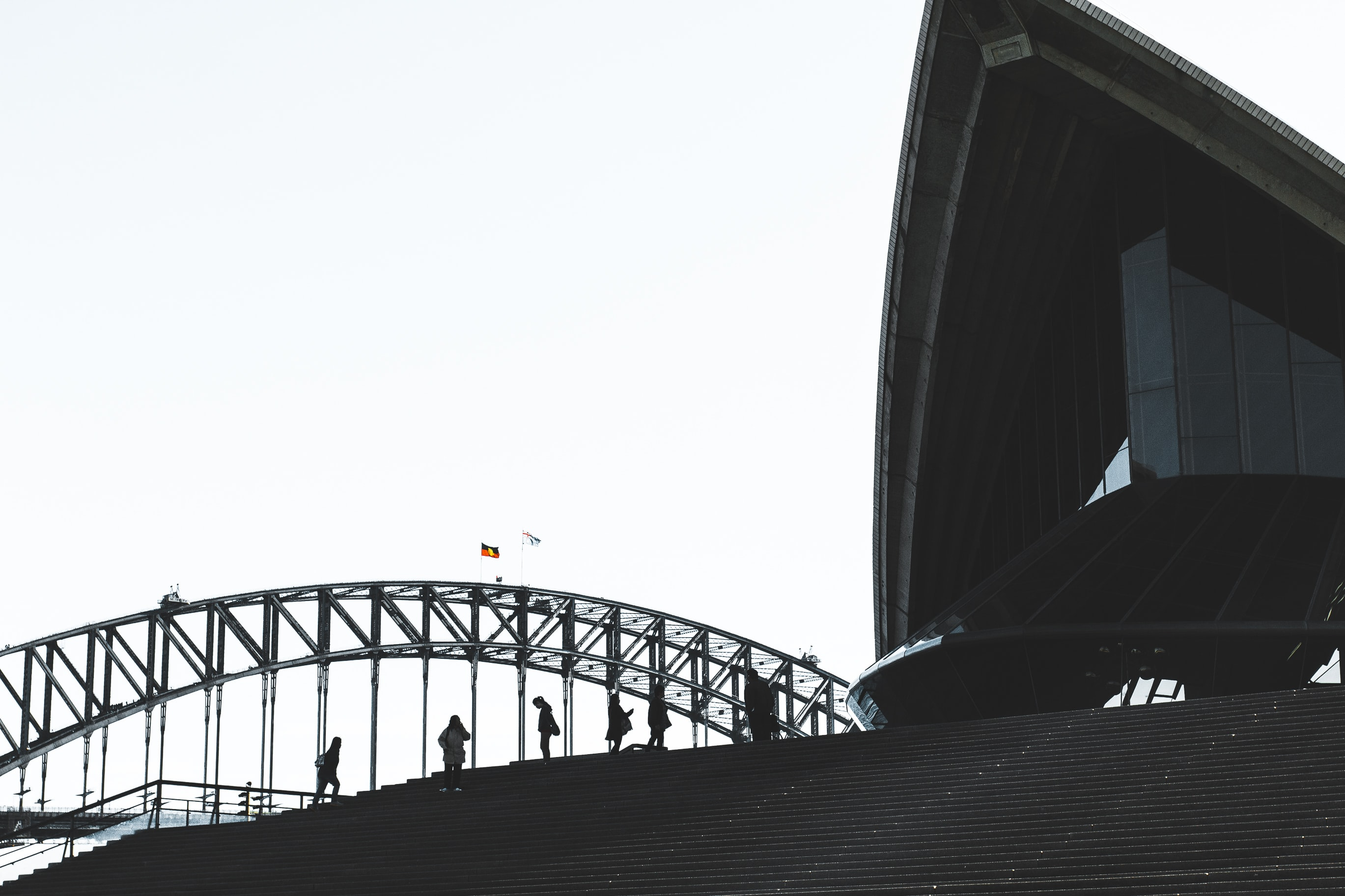 low angel photography of people standing near bridge