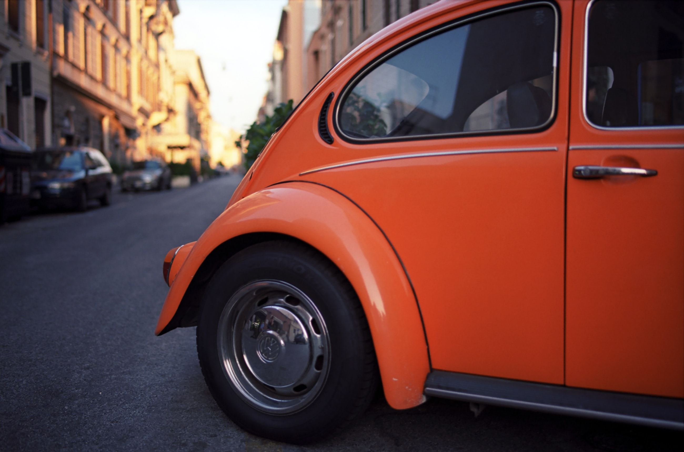 Orange vintage Volkswagen Beetle with a reflection in the back window.