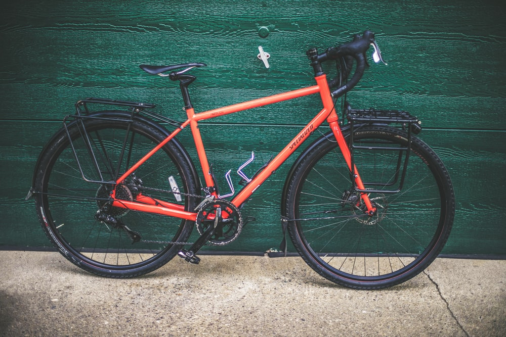 red and black road bike on green wall