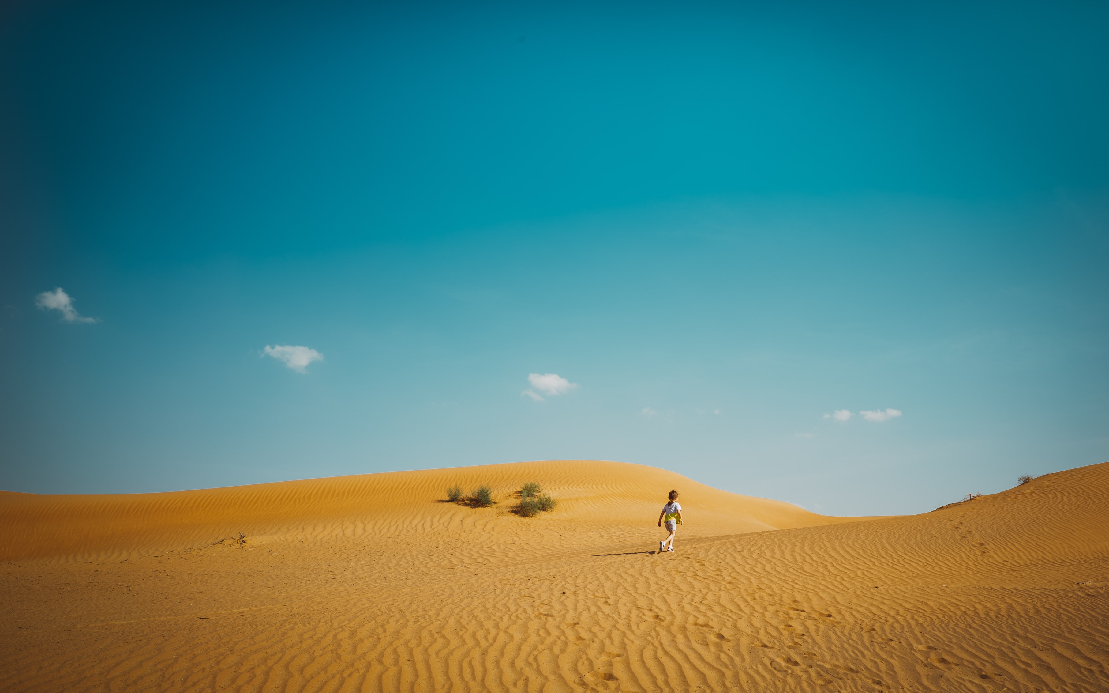 Girl walks alone in the dry sand dunes of the desert