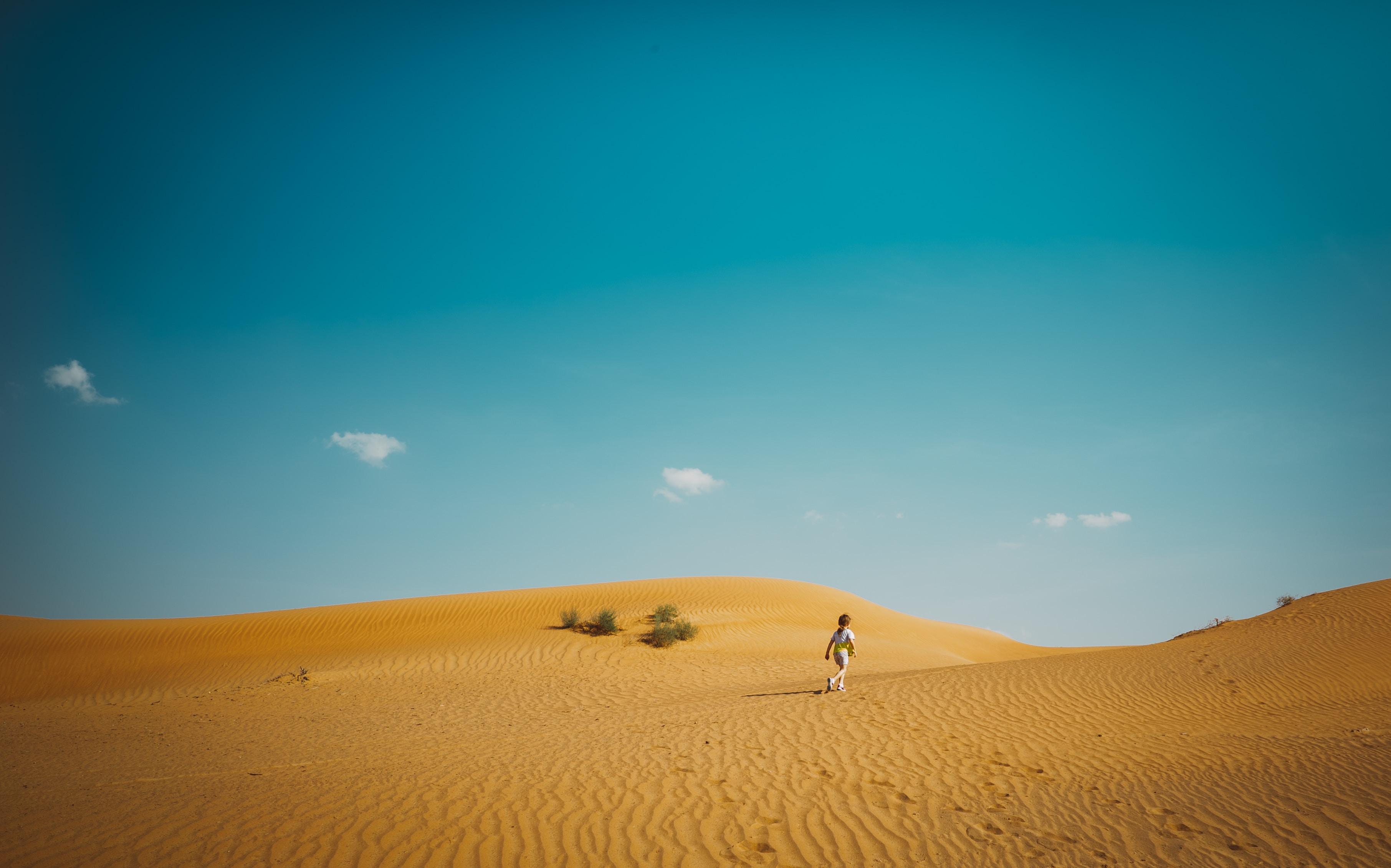 Girl walks alone in the dry sand dunes of the desert