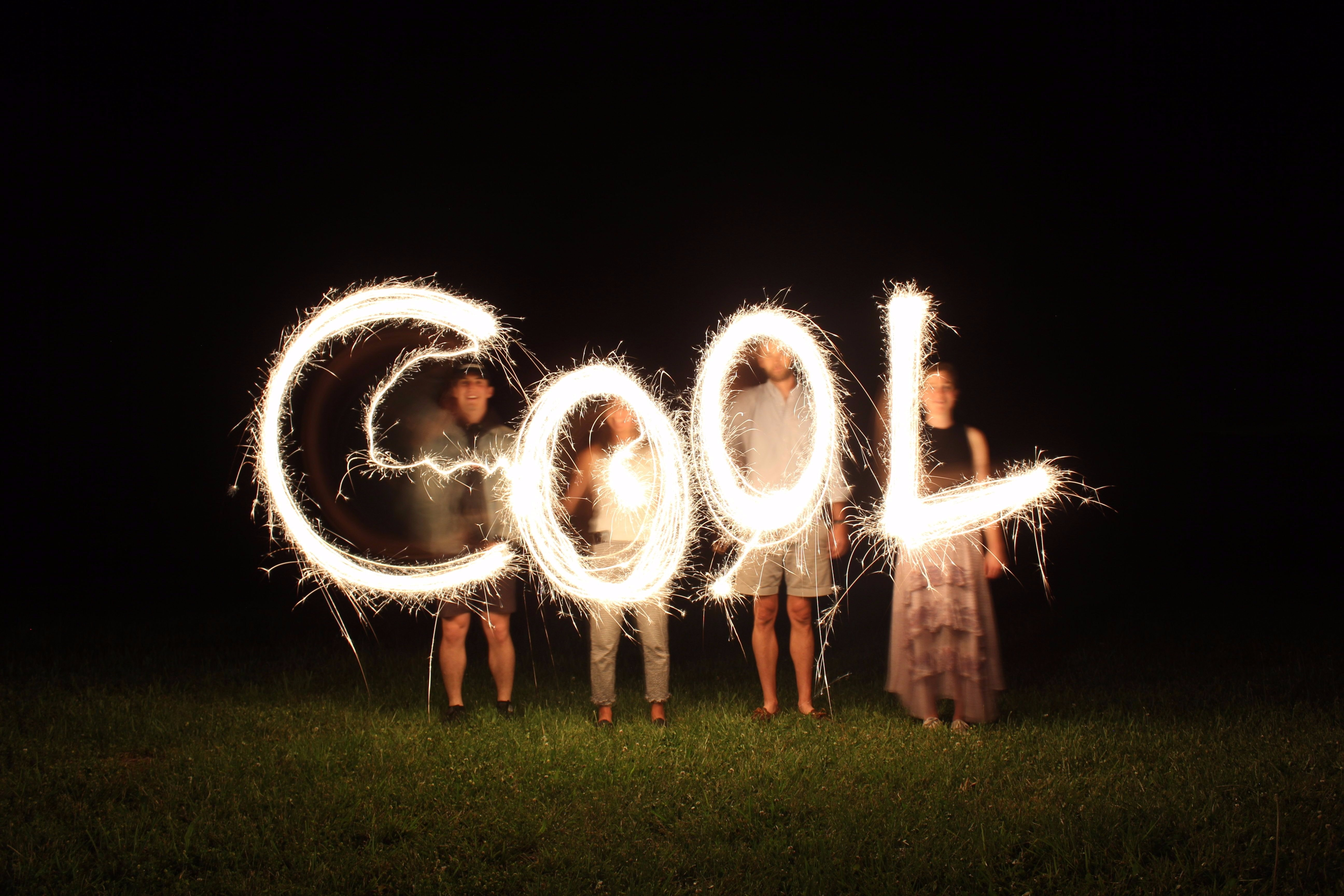 four people holding fireworks and forming cool word